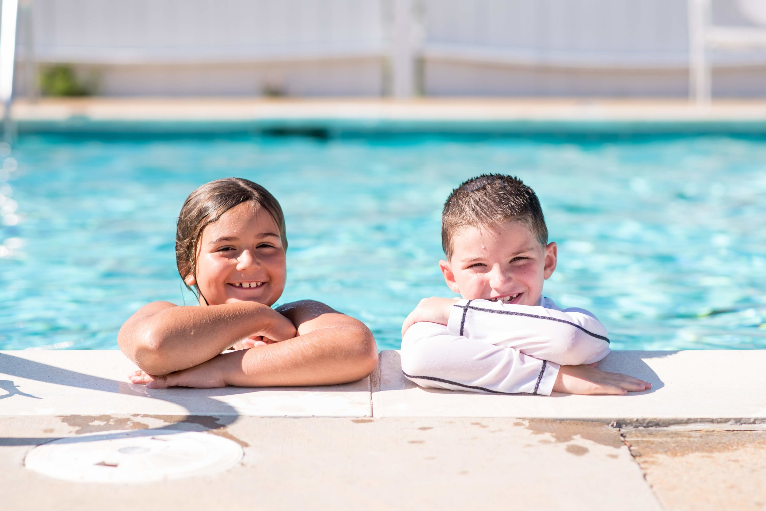 Two campers smiling at the side of the pool.