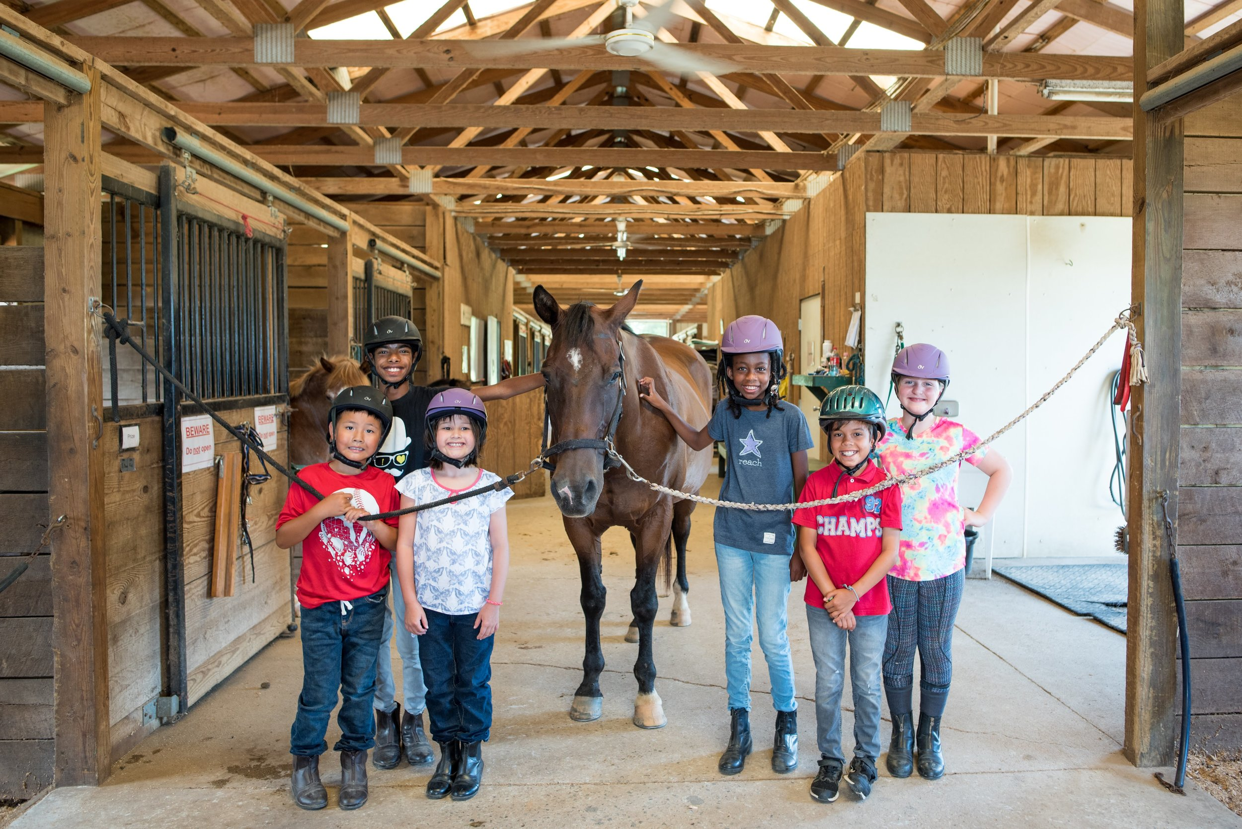 The students in riding gear smile beside one of Oakland's kind horses.