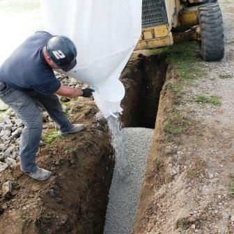 Application of AquaBlok in super sack to create a core trench to prevent lateral movement of water.