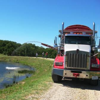 Conveyor application of AquaBlok to repair leaking pond.