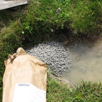 Hand application of AquaBlok to plug animal burrow on shoreline.