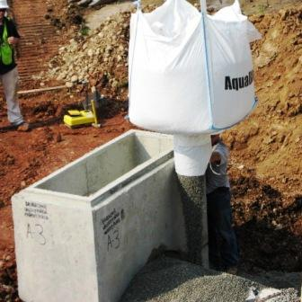 Application of AquaBlok to catch basin to protect against erosion and poor soil.