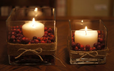 Fill glass vases and votives with cranberries and candles. Courtesy: Lady's Little Loves
