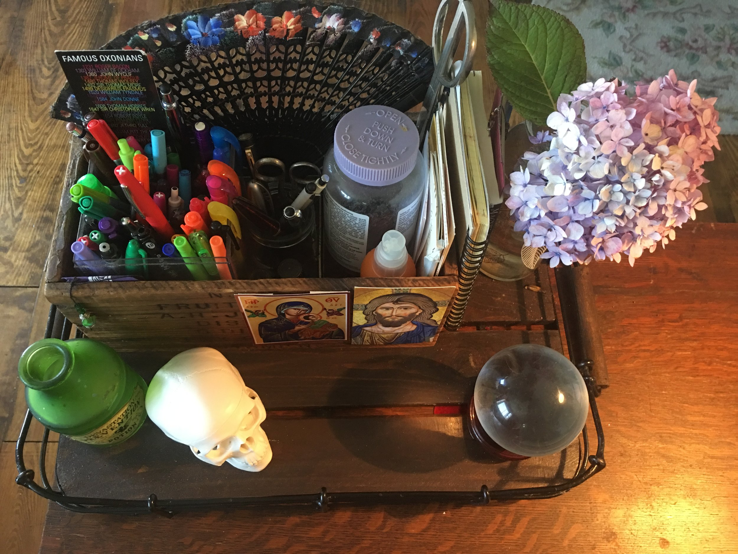 The tray that collects all my miscellaneous stuff. The skull is memento mori; the crystal ball tells me nothing about the future, but is useful to play with when I'm puzzling something out.