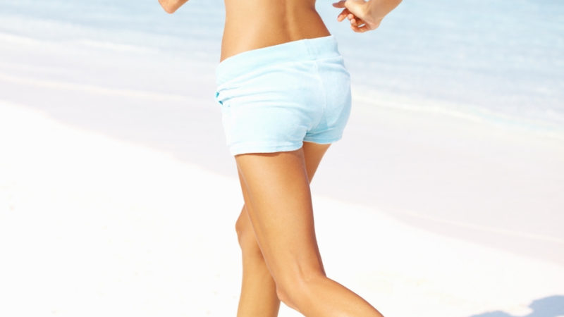 Woman running on beach for a simple interval workout.