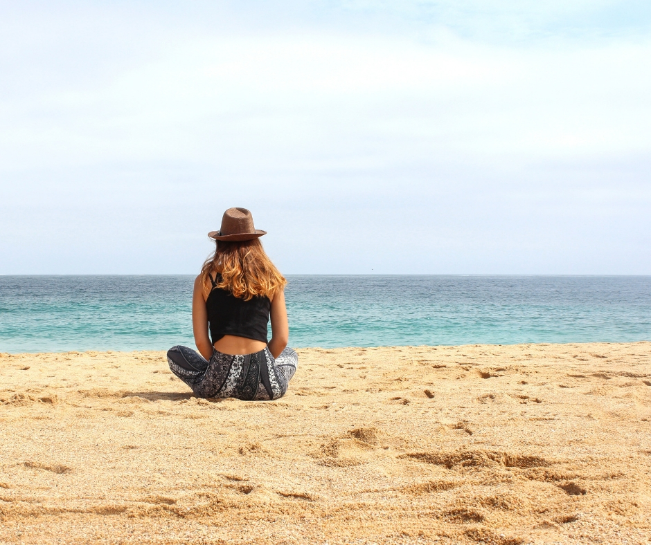 Woman sitting on the beach relaxing to reduce stress.