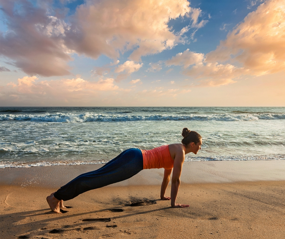 Woman doing plank on the beach as part of the core circuit.