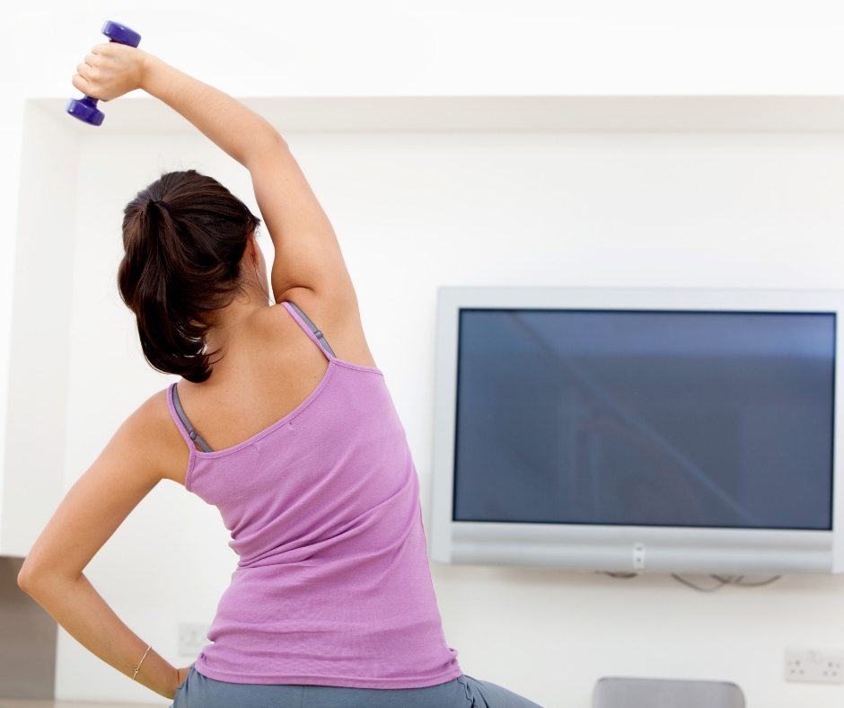 Woman uses exercise ball for at home workout.