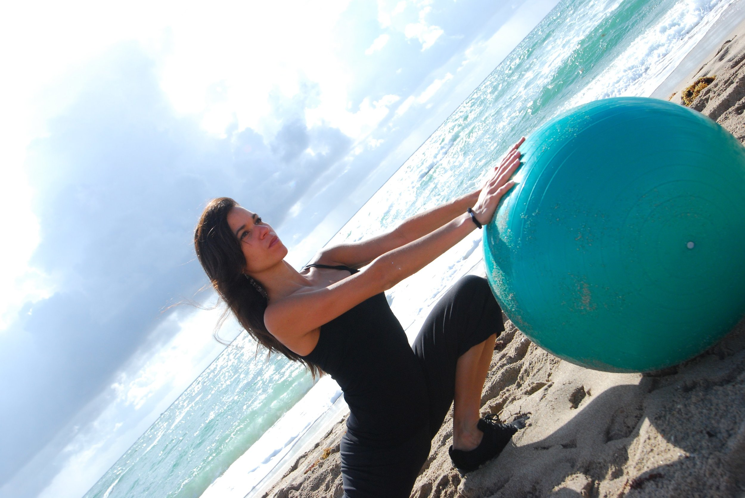 Woman with stability ball at beach during her fitness retreat.