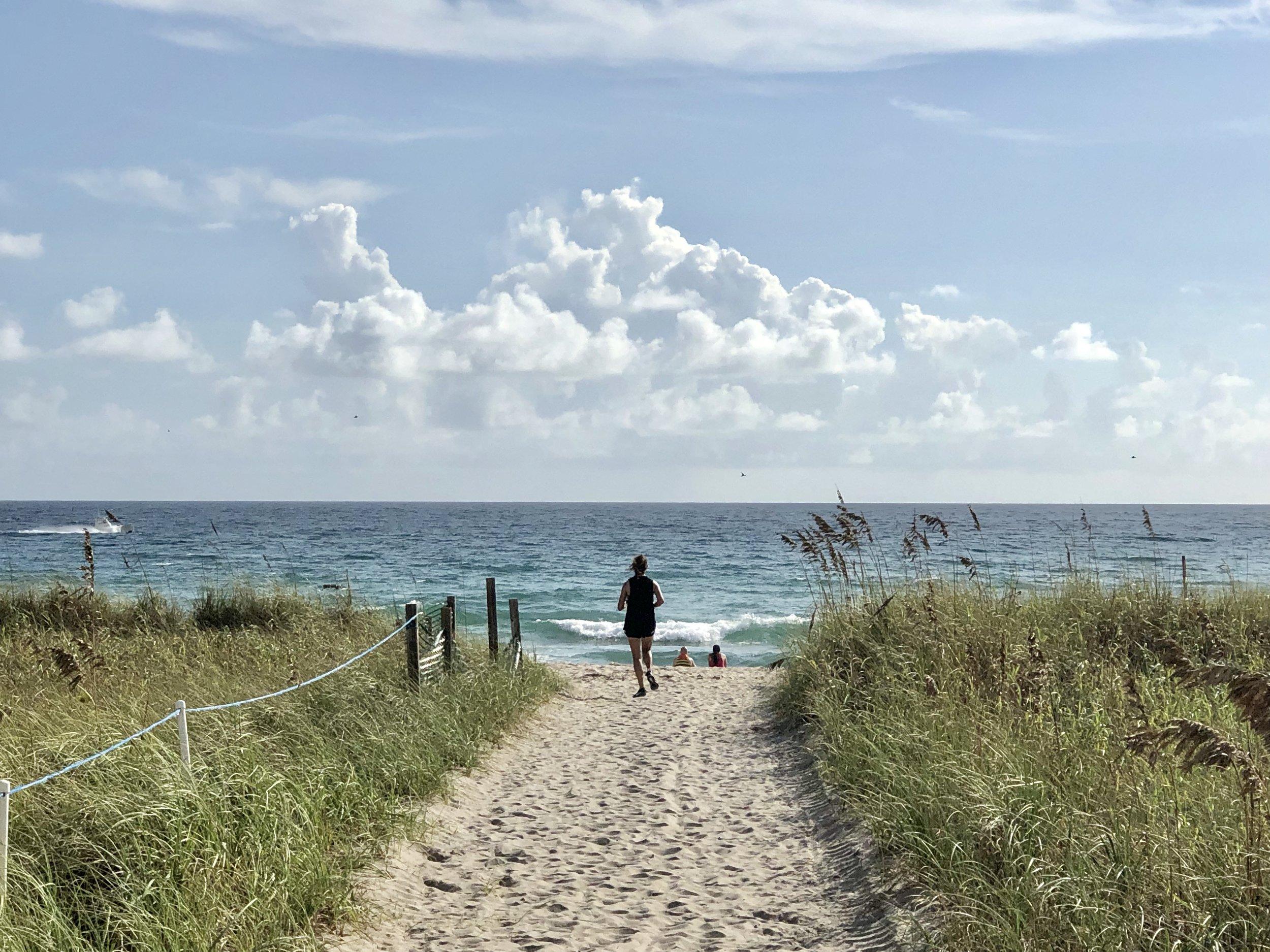 Girl running on beach during her fitness retreat.