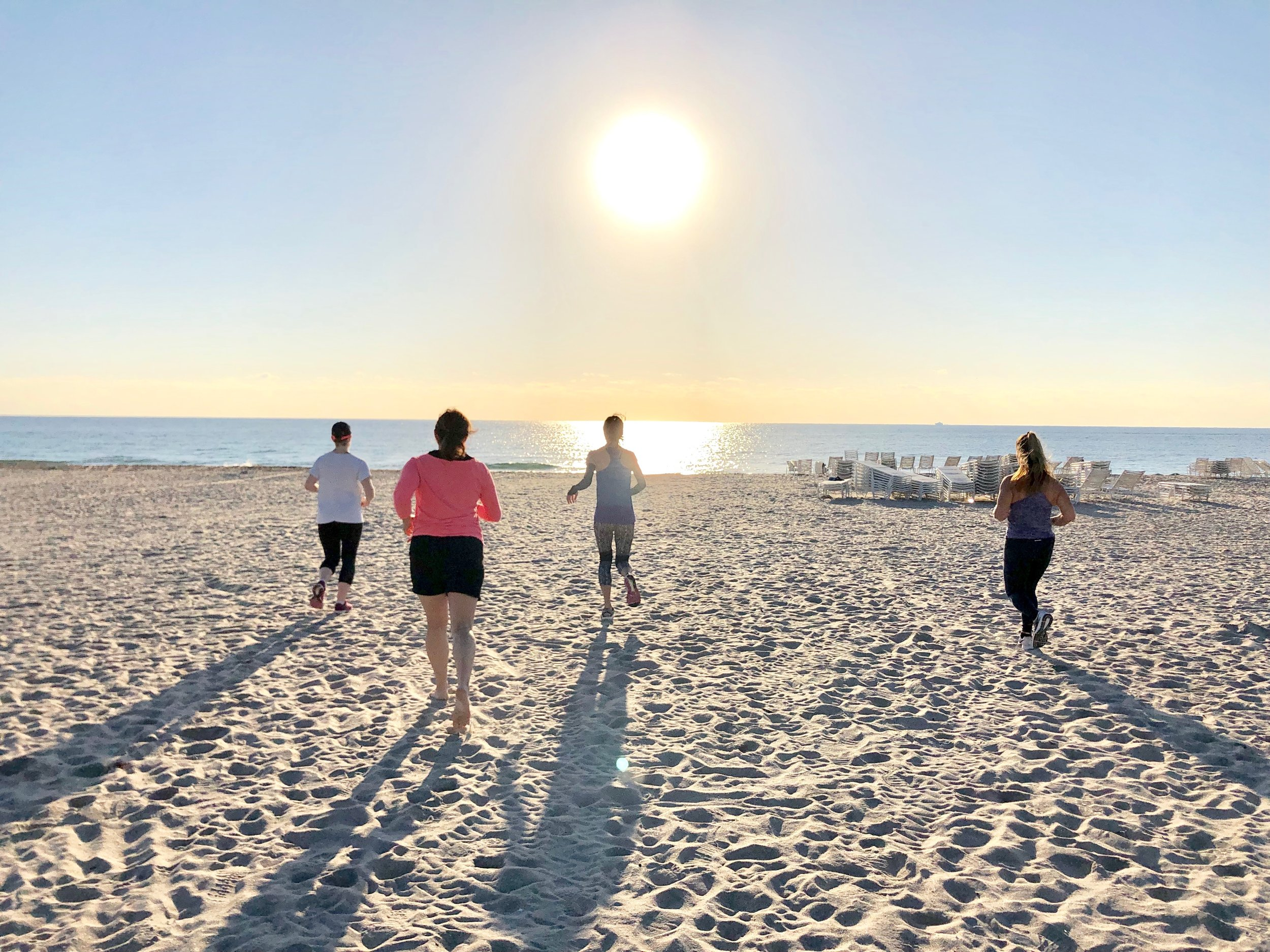 Ladies running during a fitness class on the beach in Delray Beach, FL.