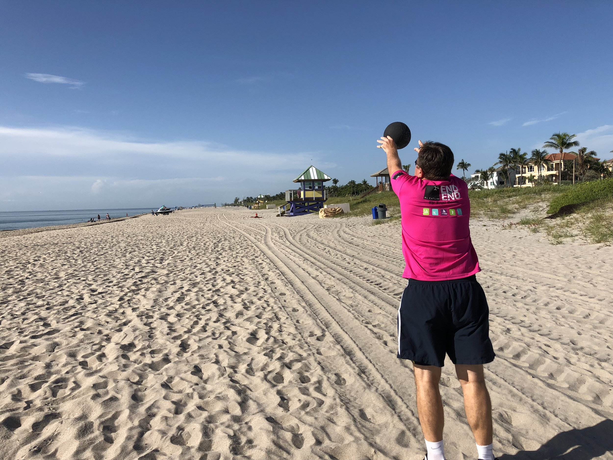 Man throws medicine ball on the beach during private retreat.