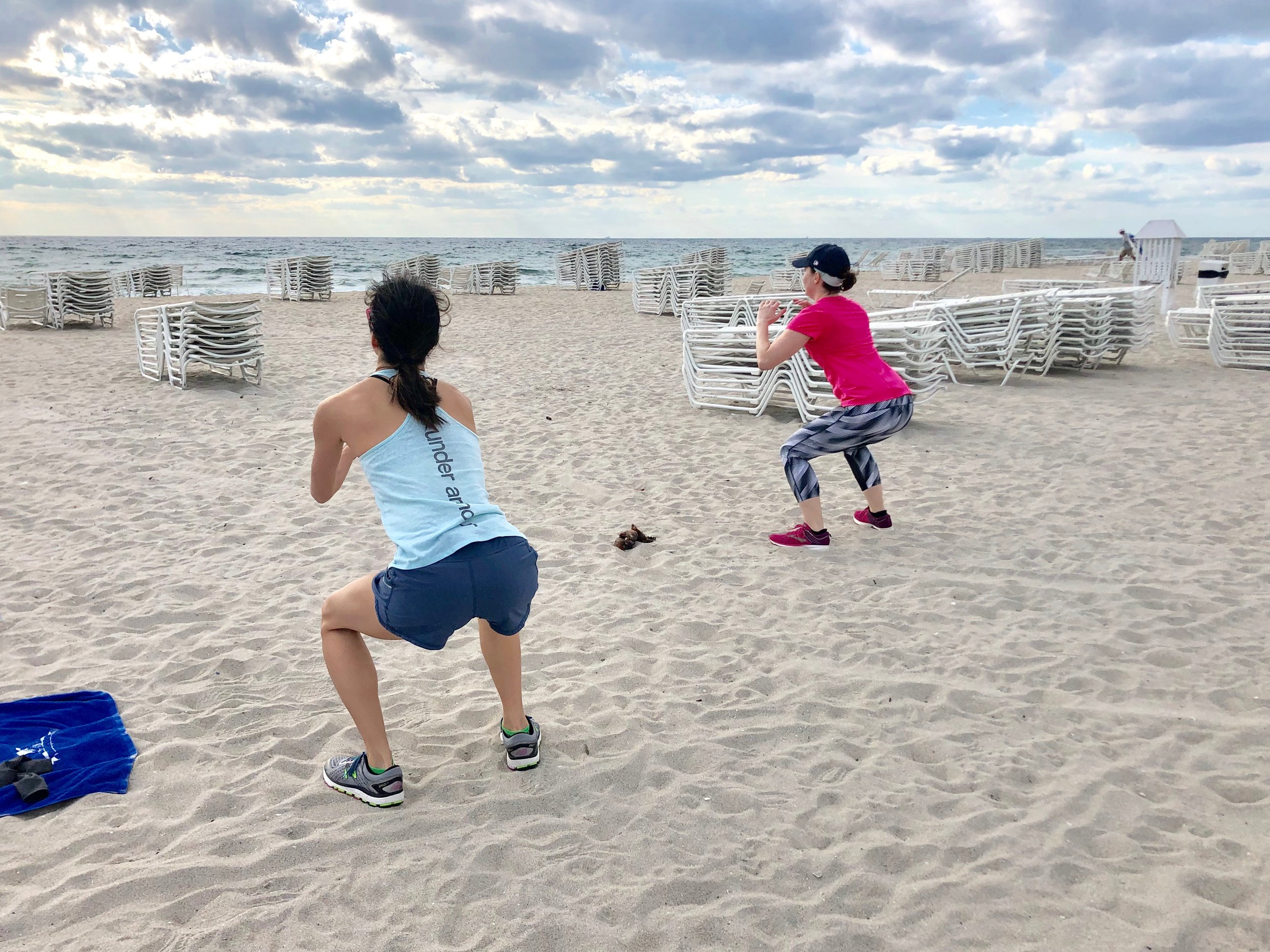 Boot camp guests do squats on the beach during bodyweight workout.