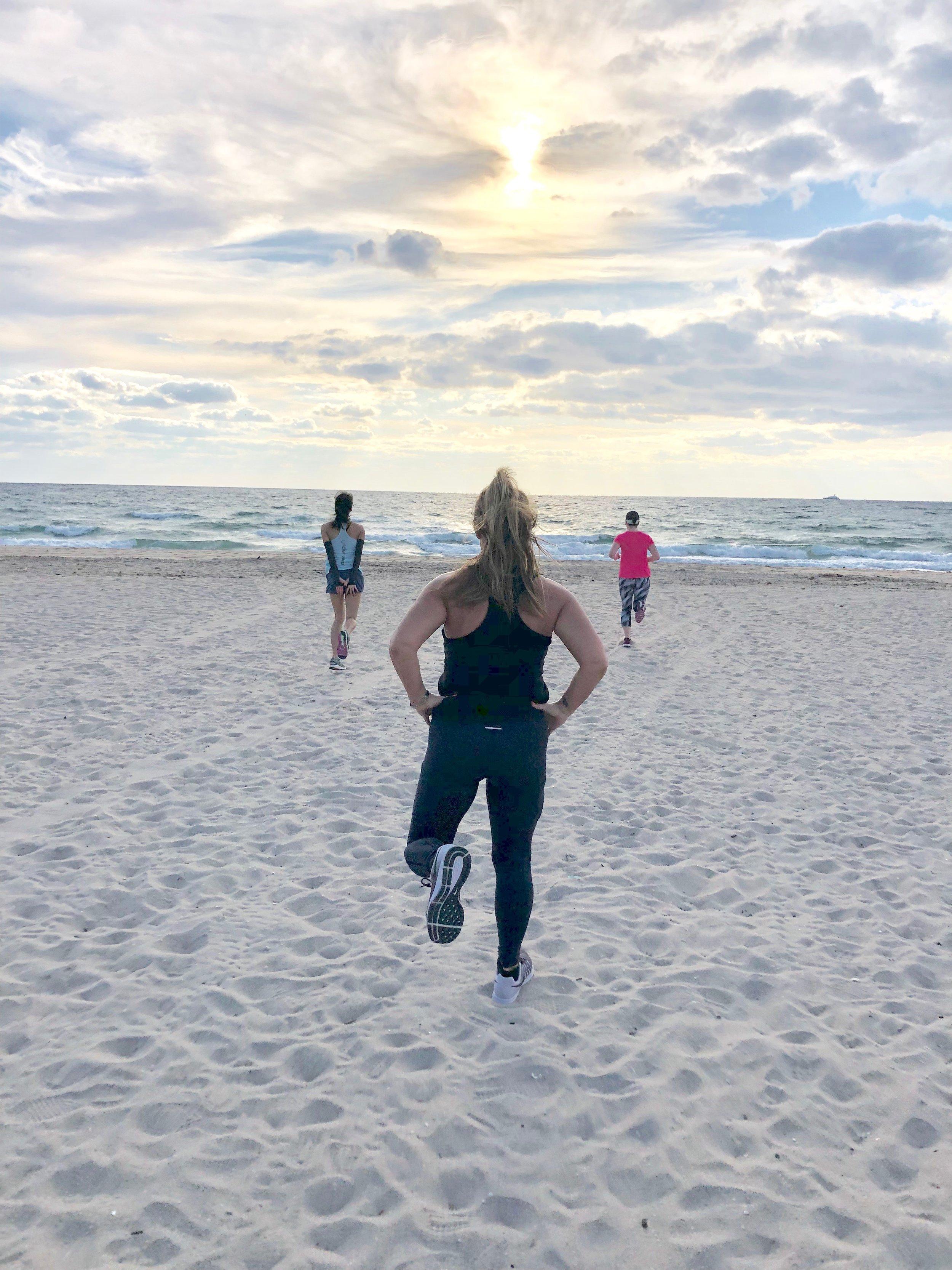 Retreat ladies do dynamic warm up on the beach.