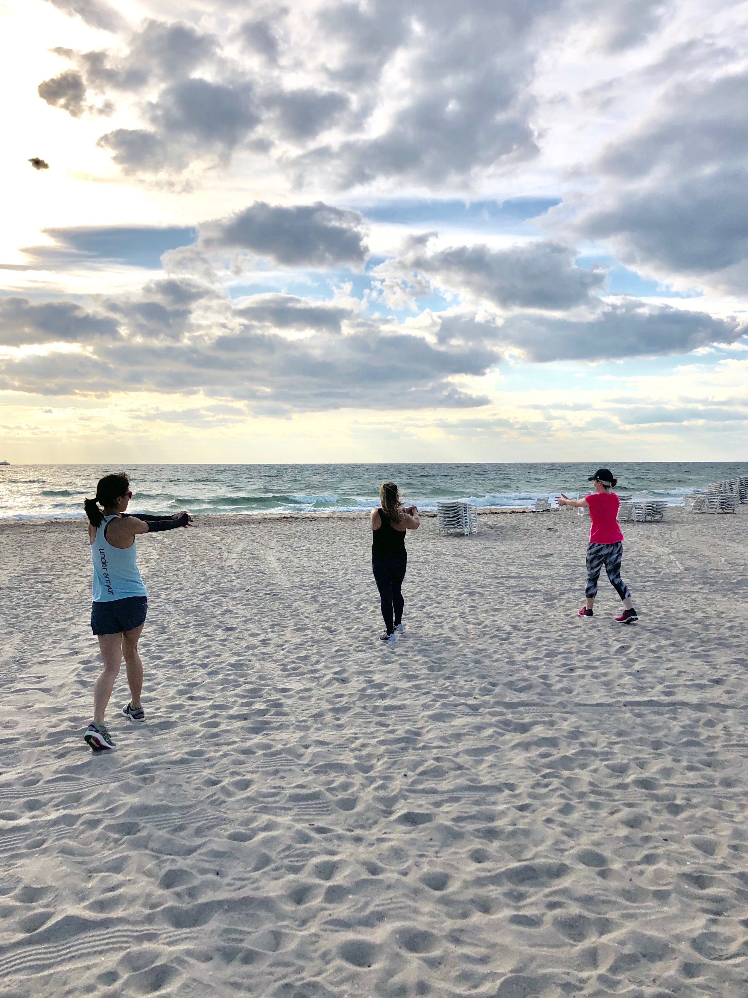 Boot camp guests workout on beach during fitness vacation.