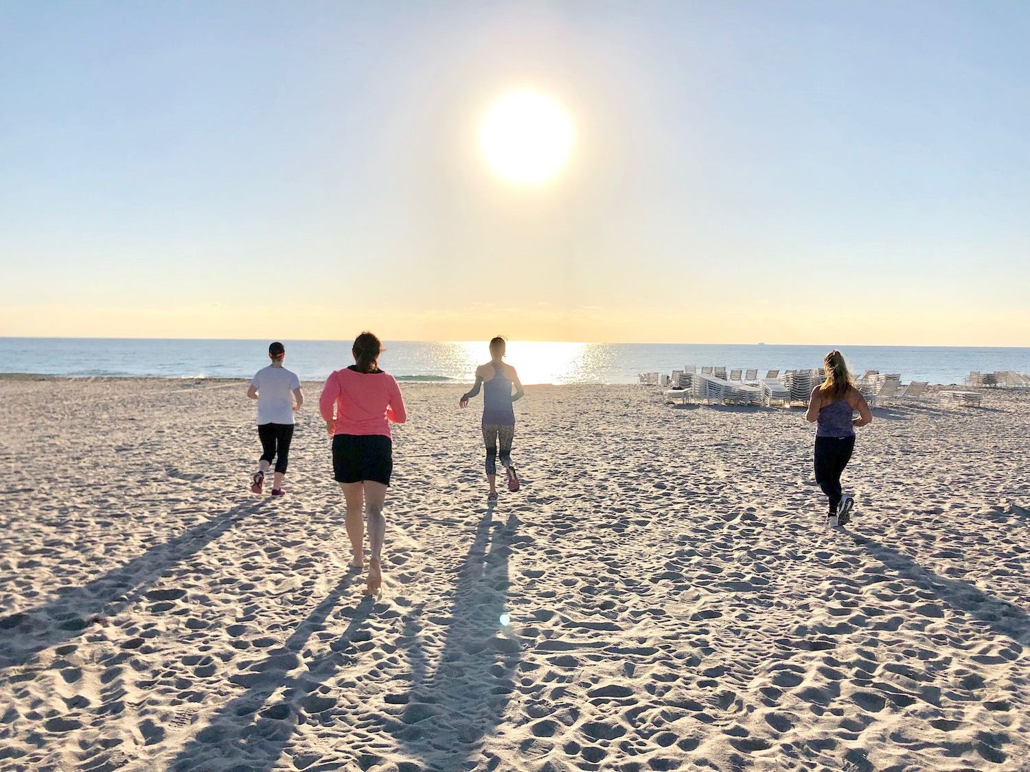 Women running during fitness retreat at the beach.