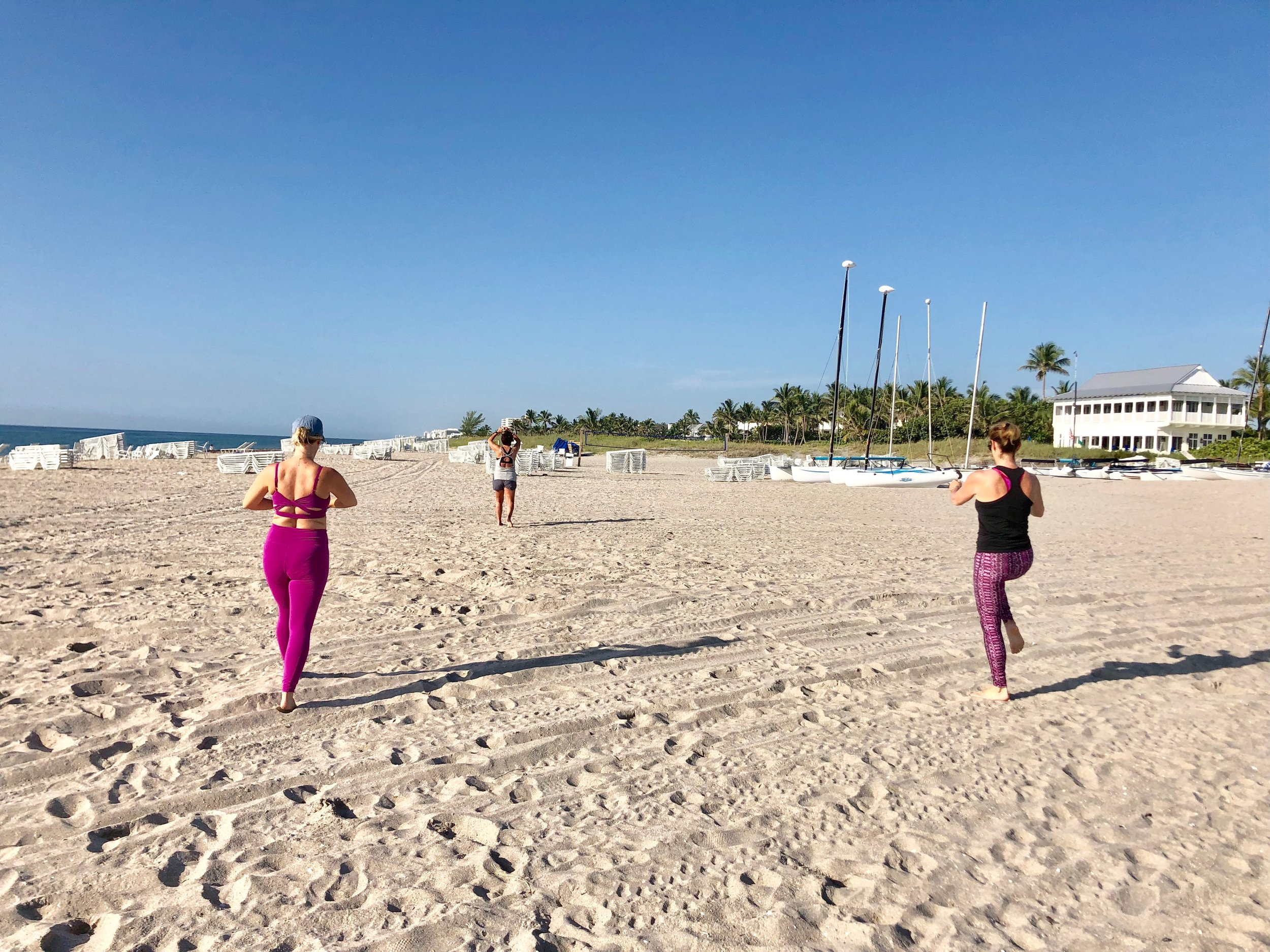 Fitness retreat ladies do morning beach workout.