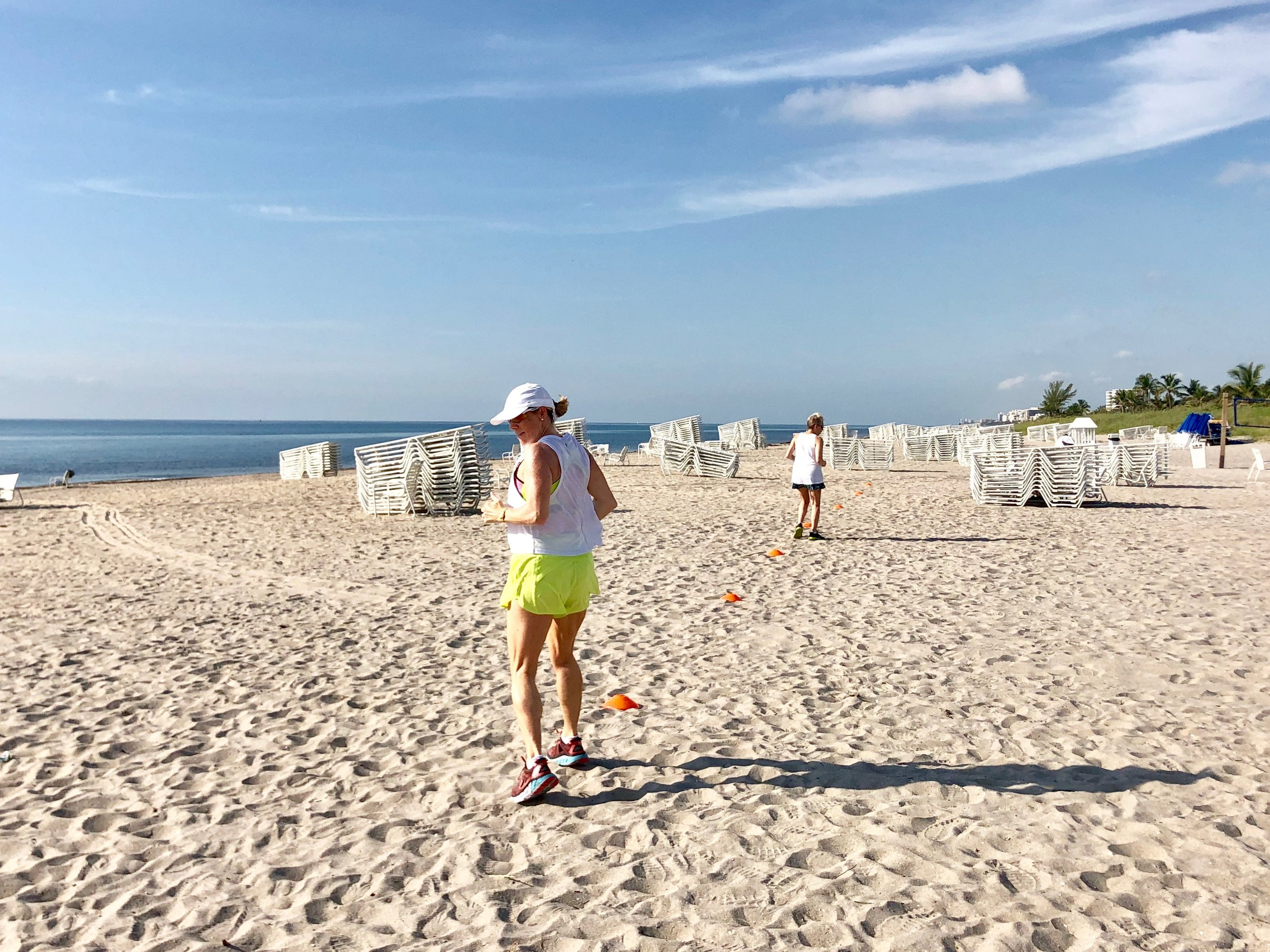 Fitness vacation guests do intervals on the beach.