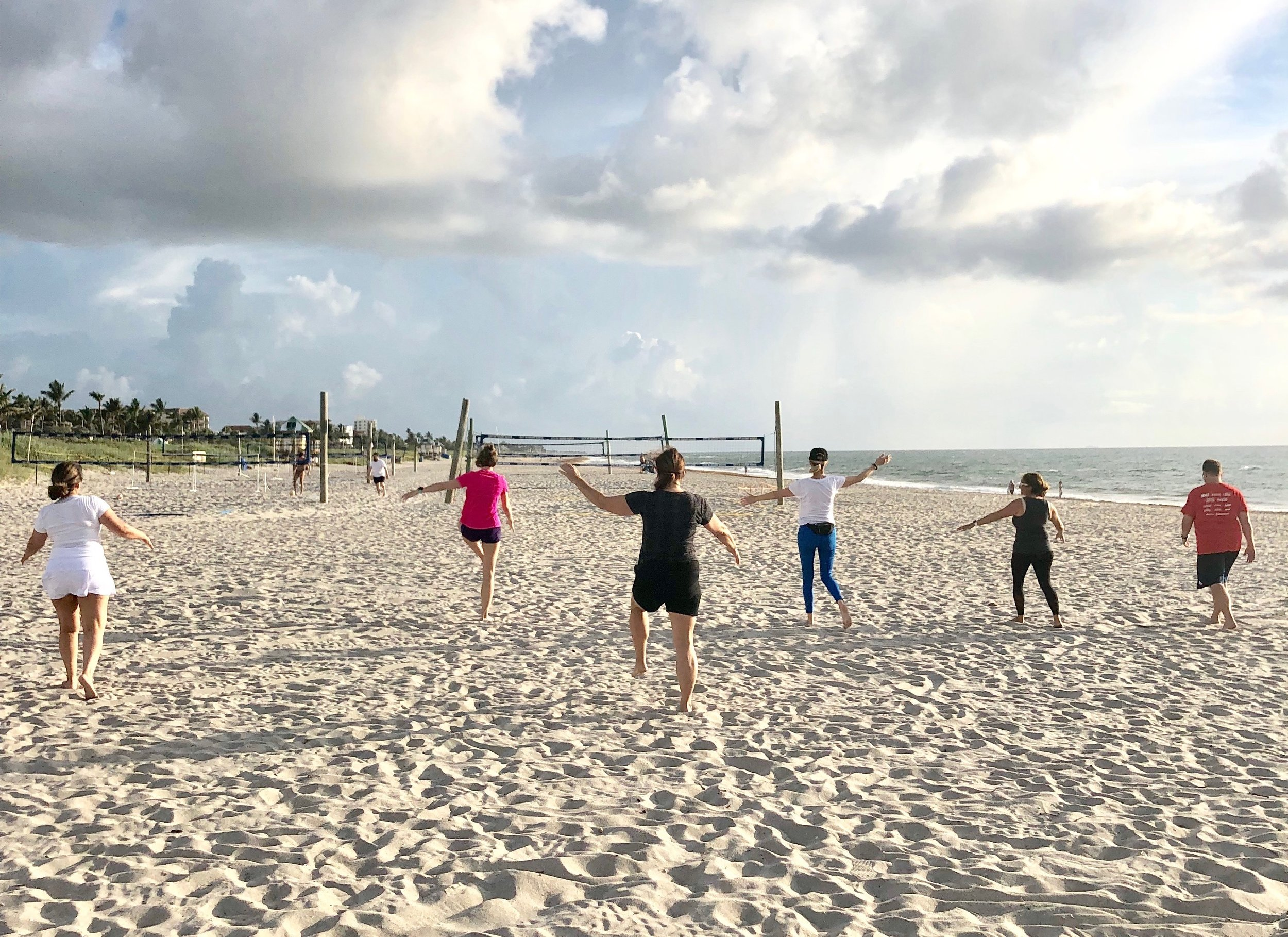 Boot camp guests enjoy a workout on the beach during their vacation.