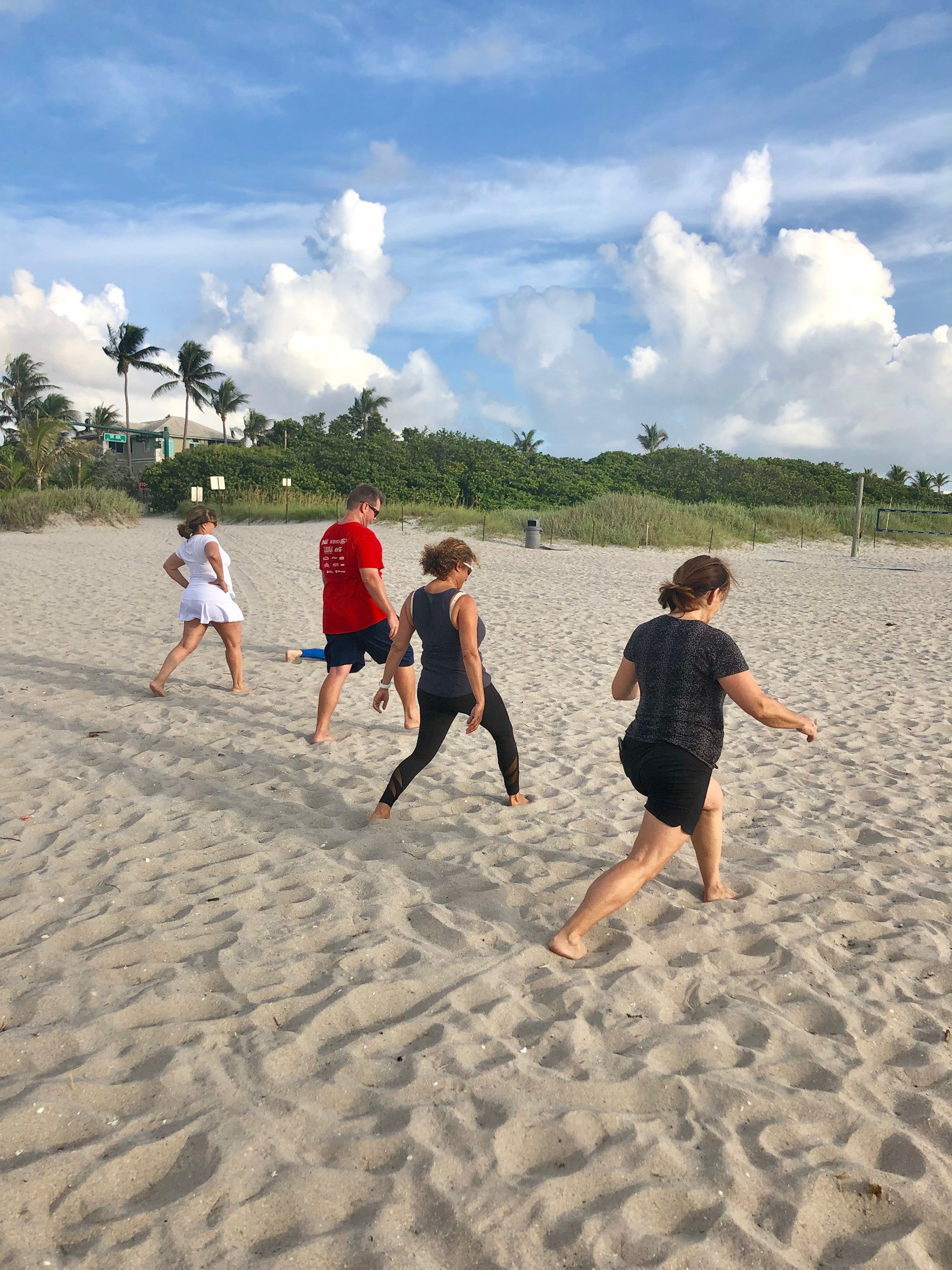 Boot camp guests lunge on the beach to reach weight loss goals.