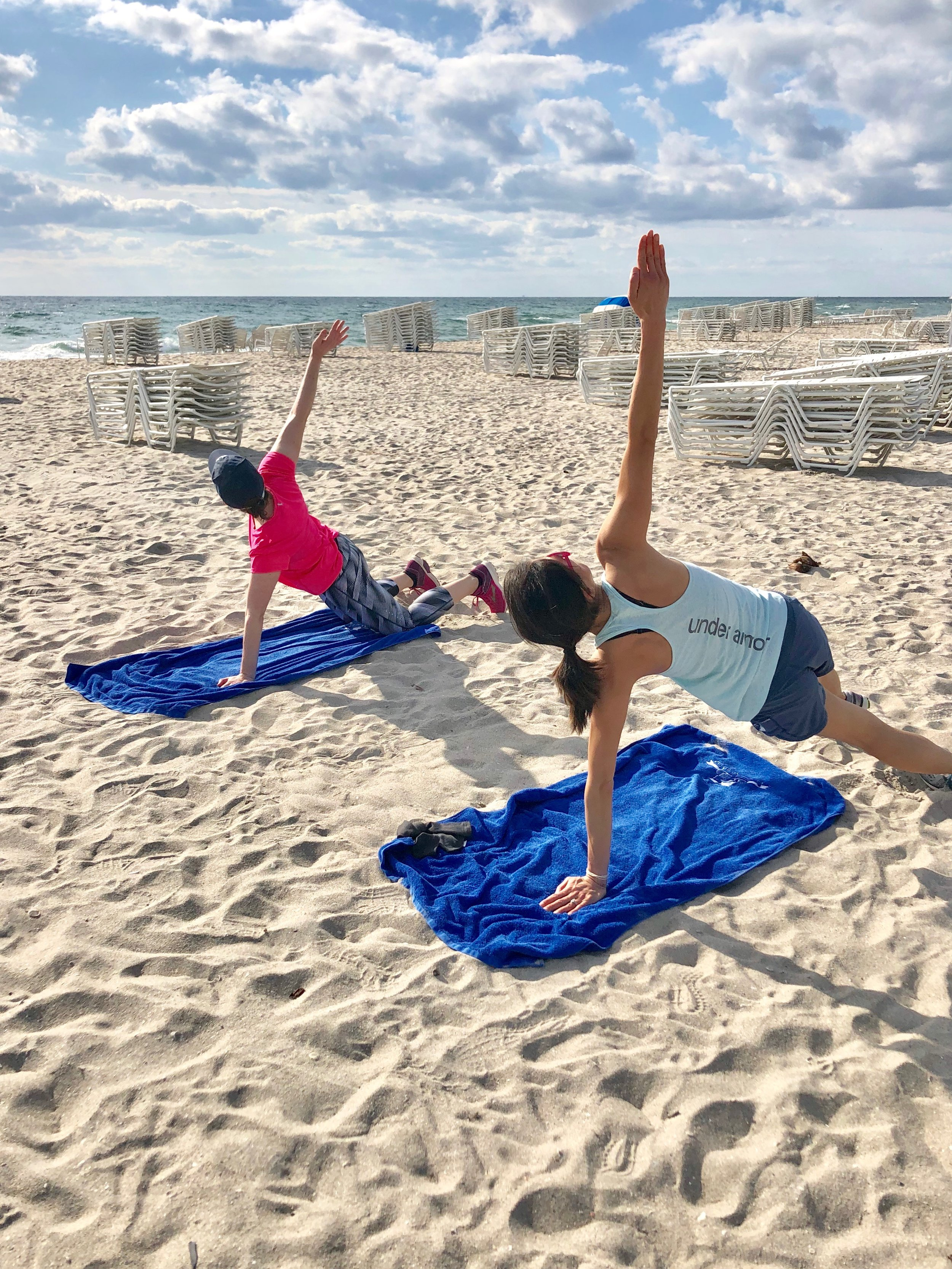 Clients enjoy core on the beach during fitness vacation.