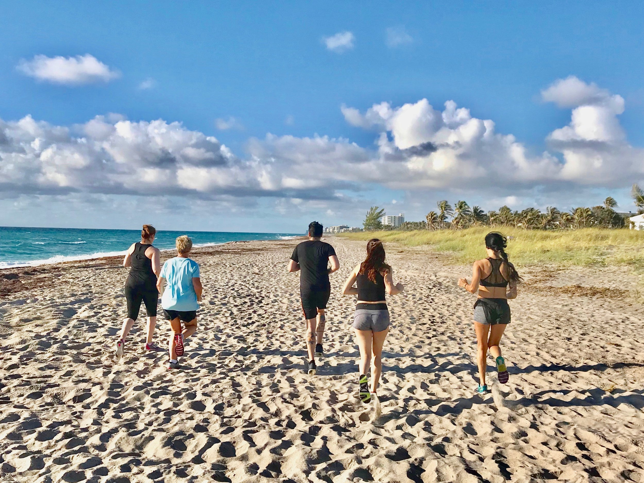 Fitness vacation guests do morning beach warm up.