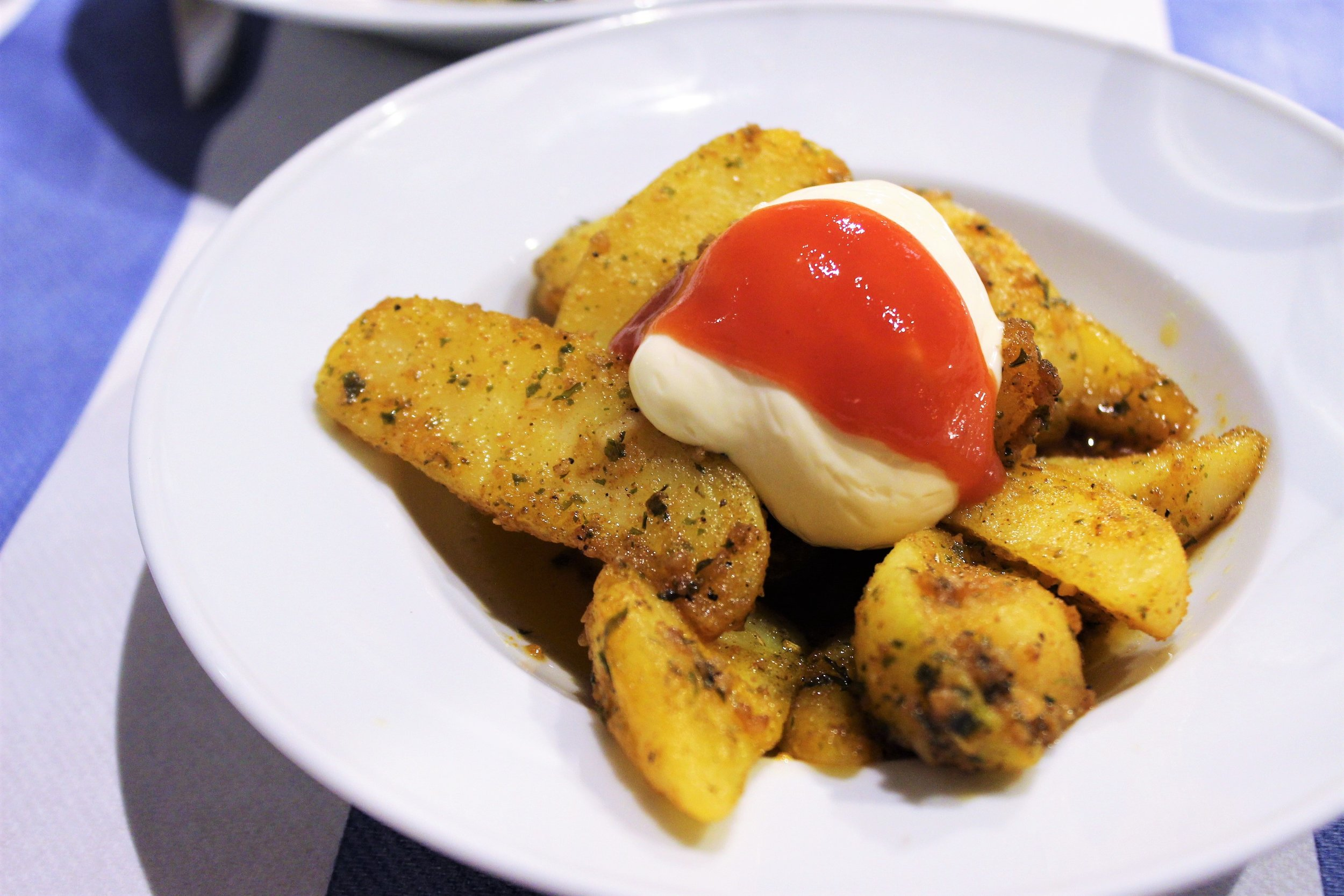 Spicy Potatoes with Mayonnaise and Salsa Brava at Gustos Bcn in Barcelona