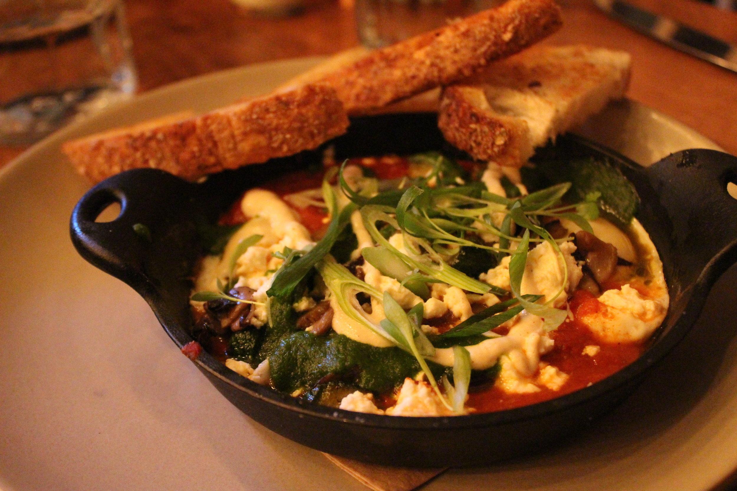 Shakshuka Egg Cast Iron Skillet (Spiced Tomato Sauce, Charred Garlic Yogurt, Herb Chutney, Feta Cheese, Zucchini, Mushrooms)
