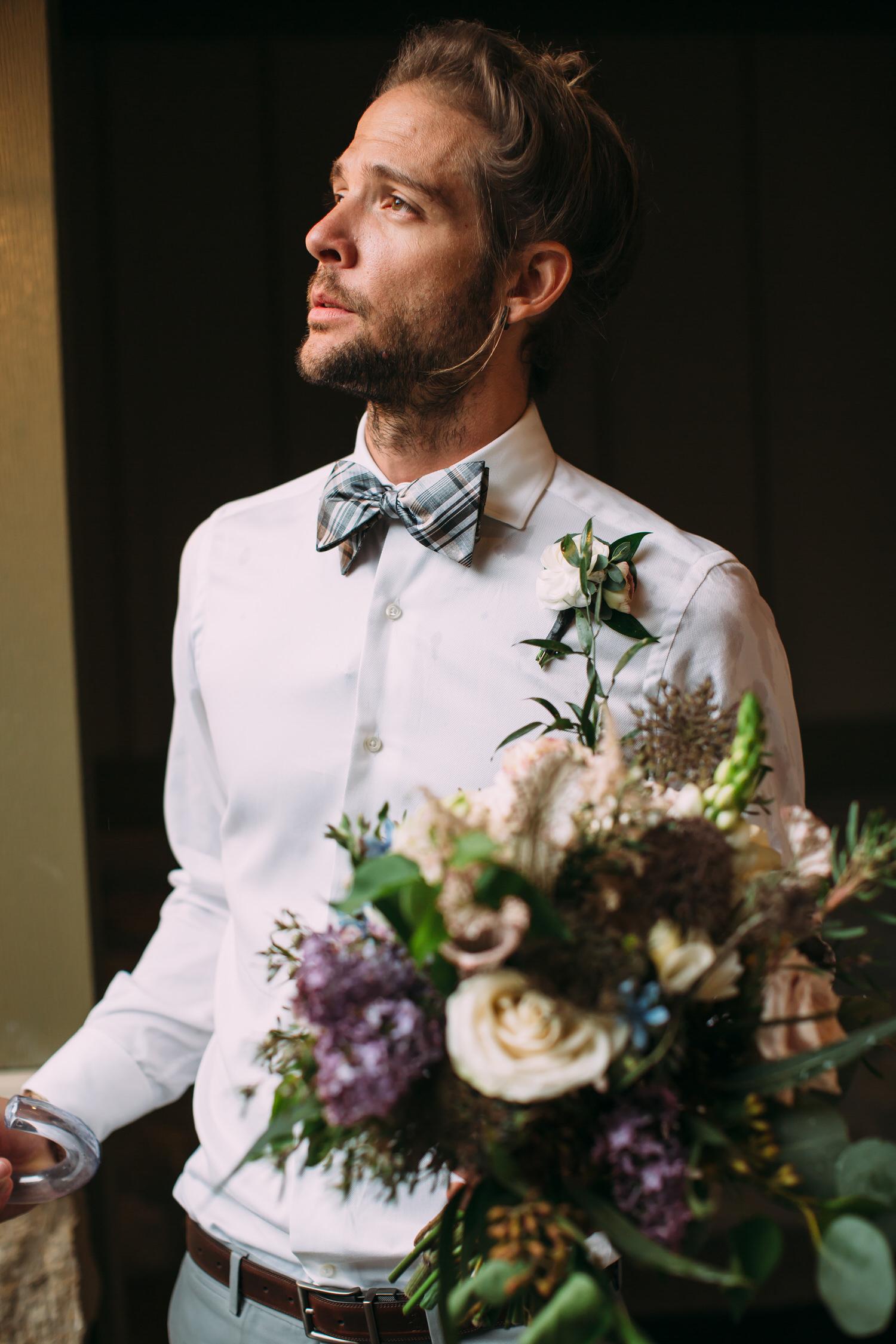 groom with man bun and wedding bouquet, France wedding photographer