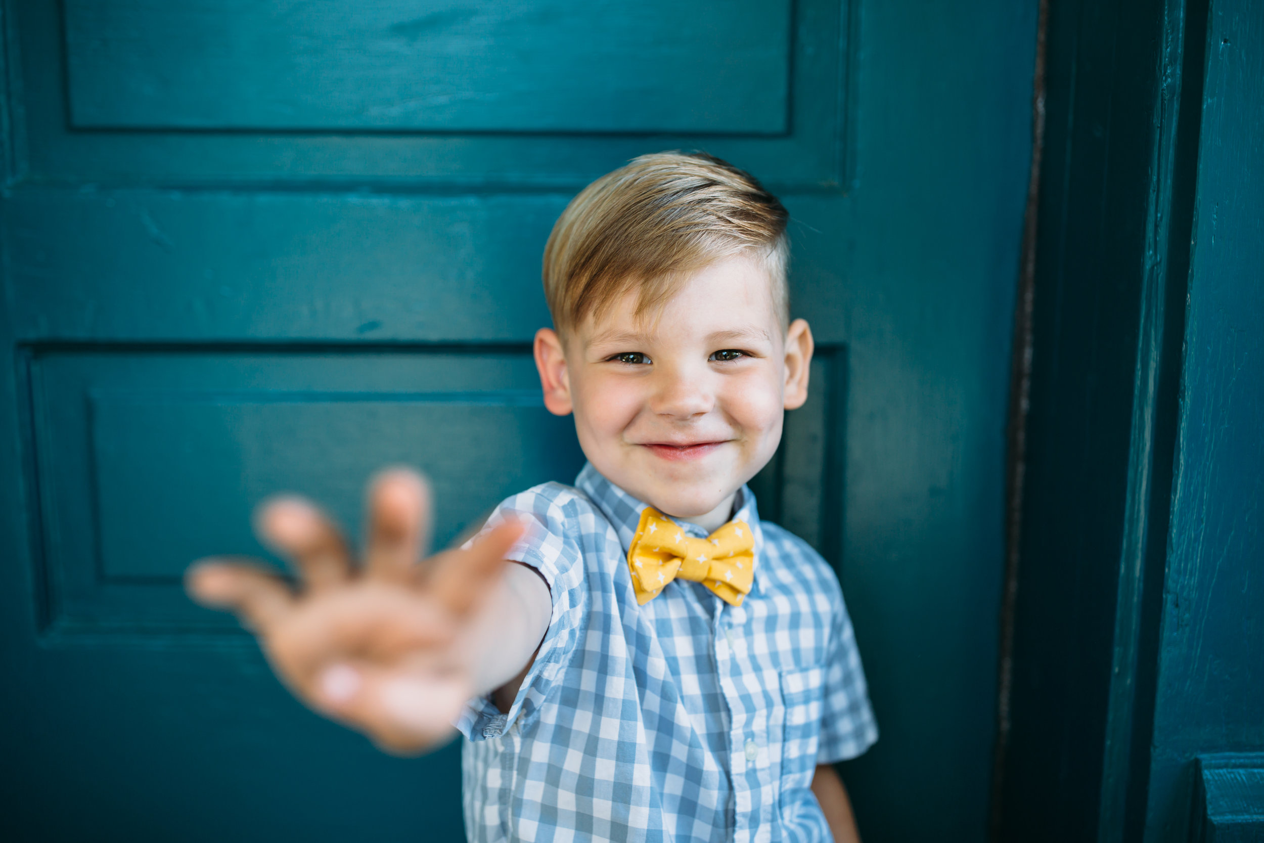 boy waving hello and smiling, fun family photos, real lifestyle photographer