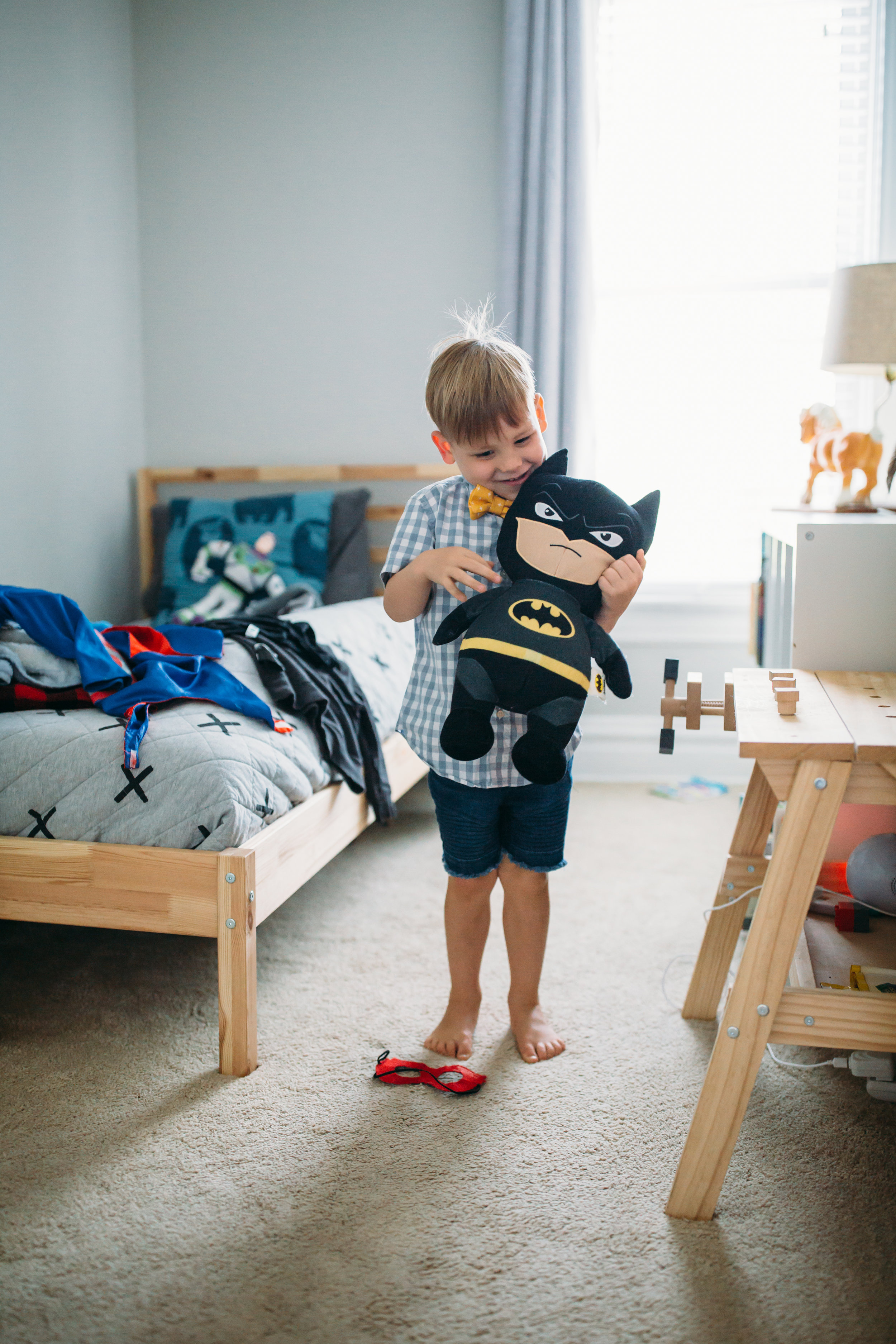 natural family photography St. Louis, at home family portraits Denver, young boy playing with batman