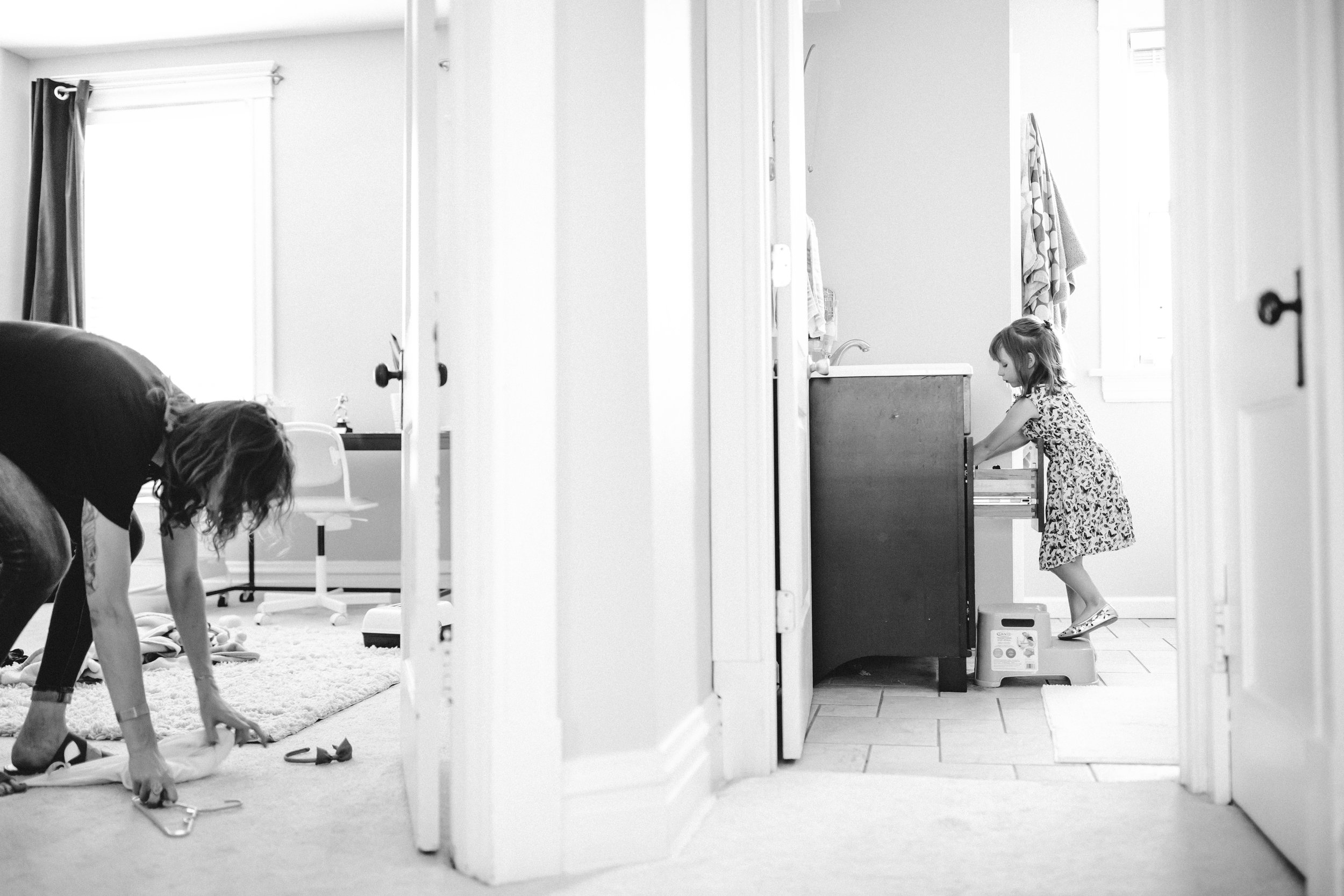 black and white photo of mother and daughter in a house, mother is on the left in the bedroom picking up toys and clothes from the ground, while across the hall young daughter, 7 years old, is stepping up on a step ladder and has her hands in the bathroom sink
