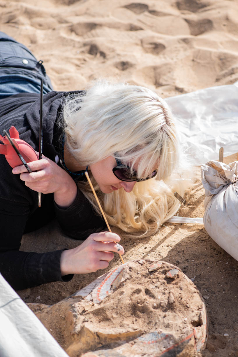 Fig. 10. Heather works on the painted exterior of the coffin. Photo: Ayman Damarany / North Abydos Expedition © 2019