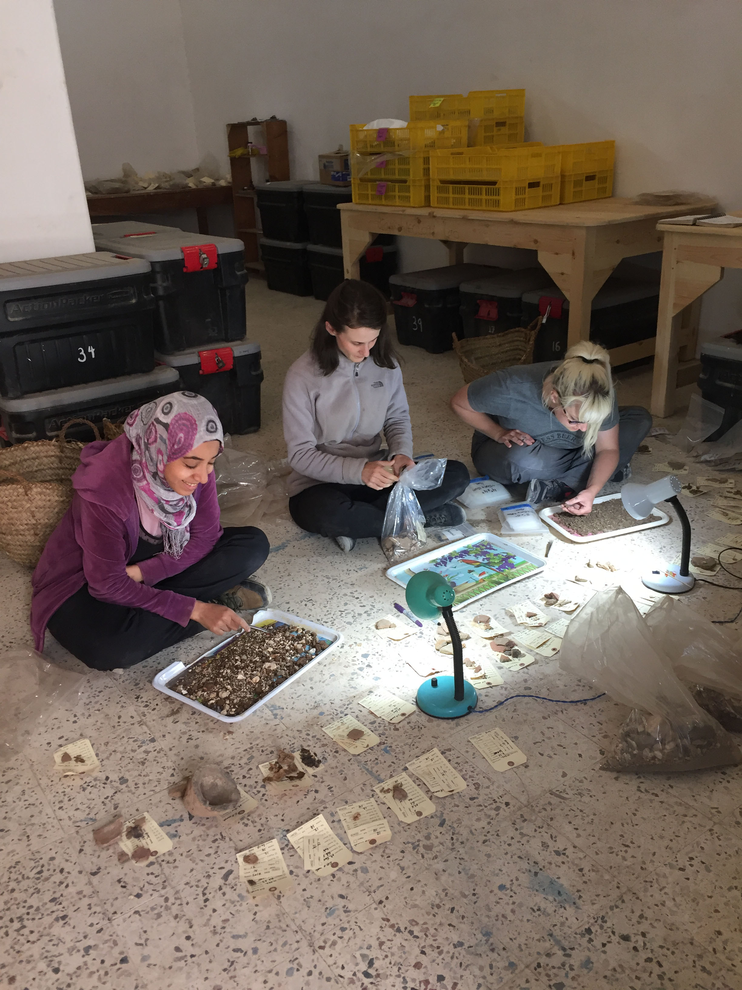 Fig. 19. Nadia Fawzy, Chantal Stein, and Heather White sift through the excavated fill of the coffin back in the bioarchaeology lab at the Abydos field house. Screening for fragments of wood, textile, bone, hair, charcoal, and seeds ensures the recovery and documentation of even the smallest artifacts. Photo: Wendy Doyon / North Abydos Expedition © 2019
