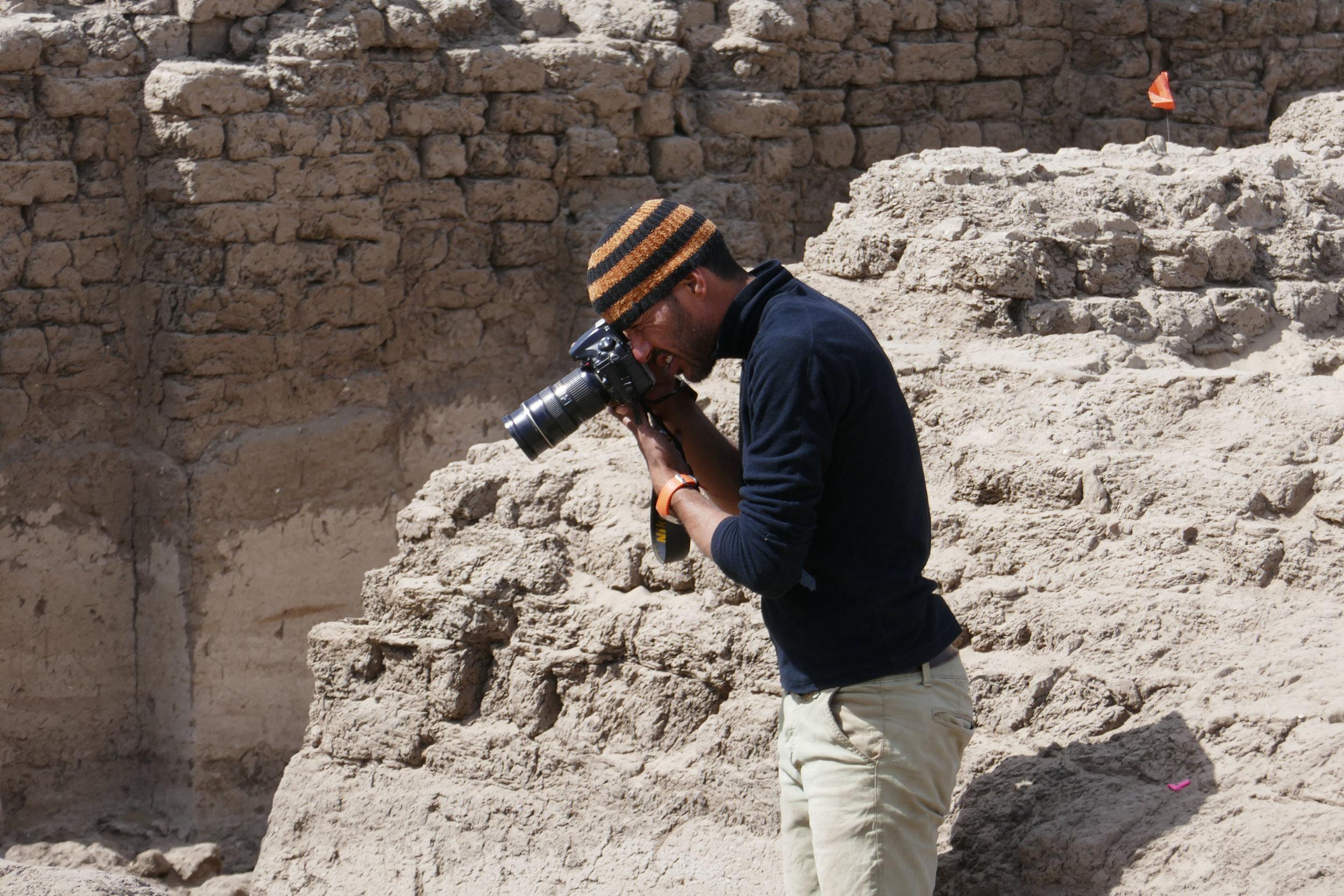 Fig. 6. Archaeologist Ayman Damarany photographing the east corner gateway at the Shunet el-Zebib. Photo: Kay Barnett / North Abydos Expedition © 2019