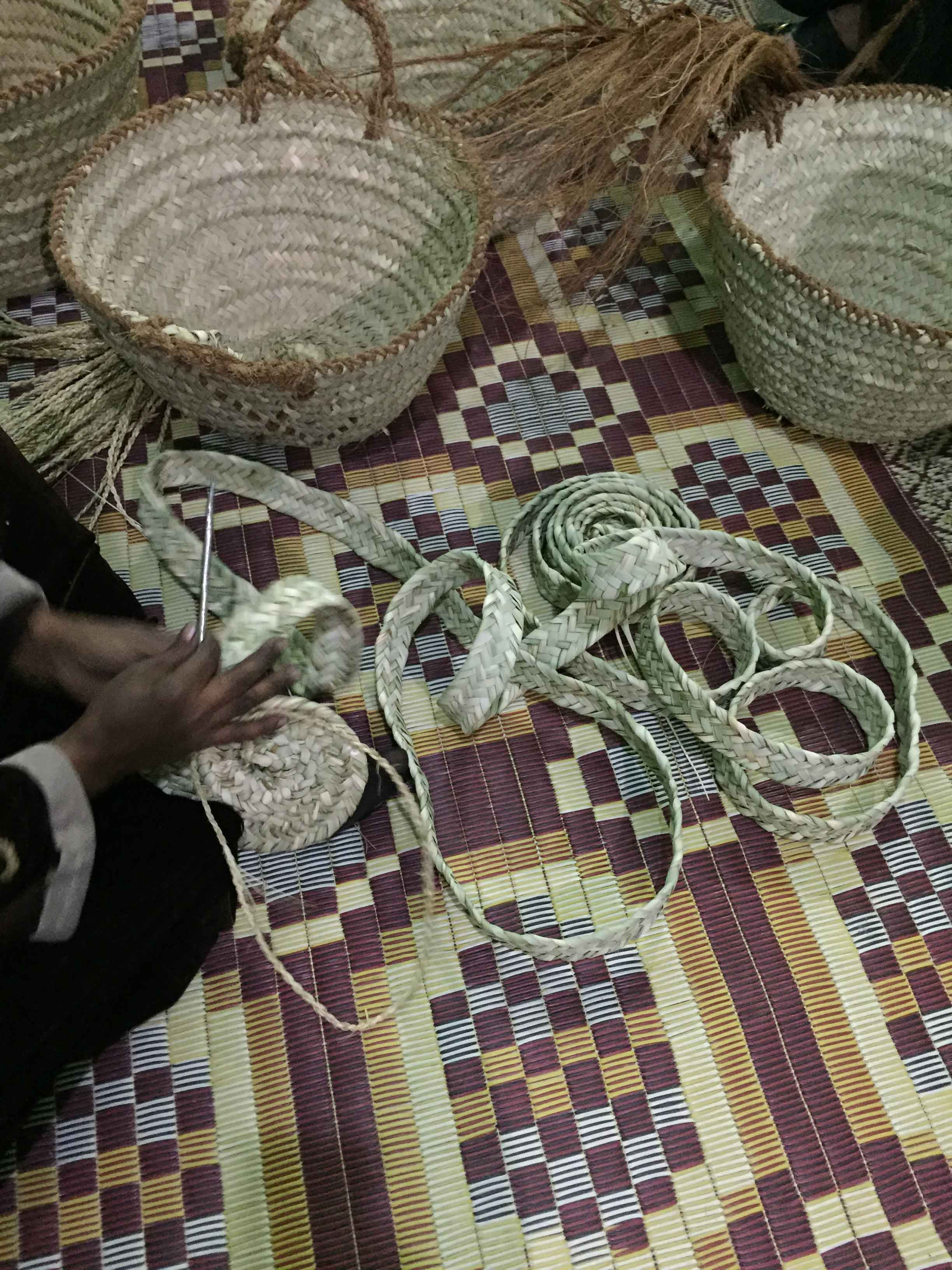 "Fig. 13. A long, woven band of palm fibers sits uncoiled, ready to be sewn into the shape of a basket — behind it an example of the ""white"" basket made from the inner part of the palm leaf (upper left) and the cheaper ""green"" basket made from the outer part of the leaf (upper right). Photo: Wendy Doyon / North Abydos Expedition © 2019"