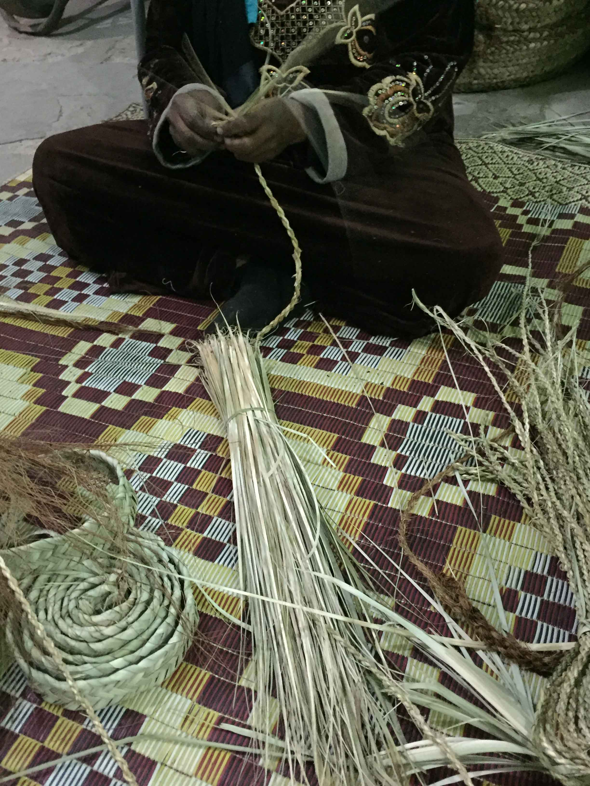 Fig. 15. Rolled band of pressed, woven, soaked, and cleaned palm fronds that will become a basket (left) next to a bunch of rough-cut palm fronds (center) used to make the braided twine (right) that serves as thread for sewing the basket together. Photo: Wendy Doyon / North Abydos Expedition © 2019