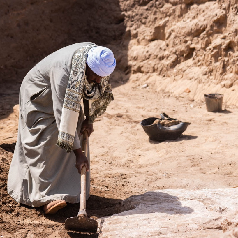 Fig. 2. Ashraf Zeydan Mahmoud — a top archaeological technician from Quft & one of the longest-excavating members of the team at Abydos — uses a  tureya  to define the edge of a stone block at the Osiris Temple pylon. Photo: Ayman Damarany / North Abydos Expedition © 2019