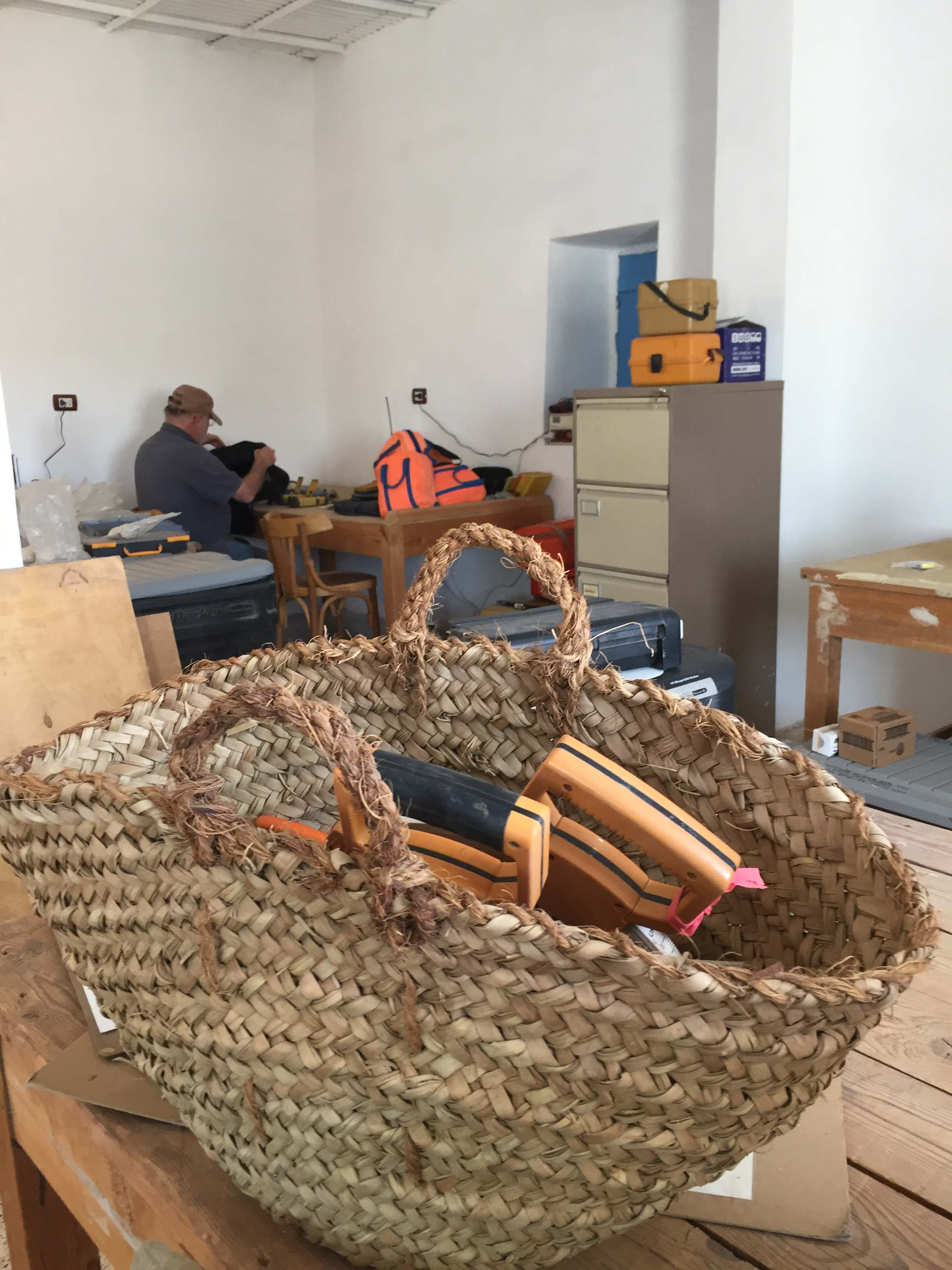 Fig. 4. Not only is the  maqtaf , a traditional palm-leaf basket, used in the collection and transport of artifacts on site — it is a ubiquitous feature of laboratory life at Abydos, as well. Photo: Wendy Doyon / North Abydos Expedition © 2019