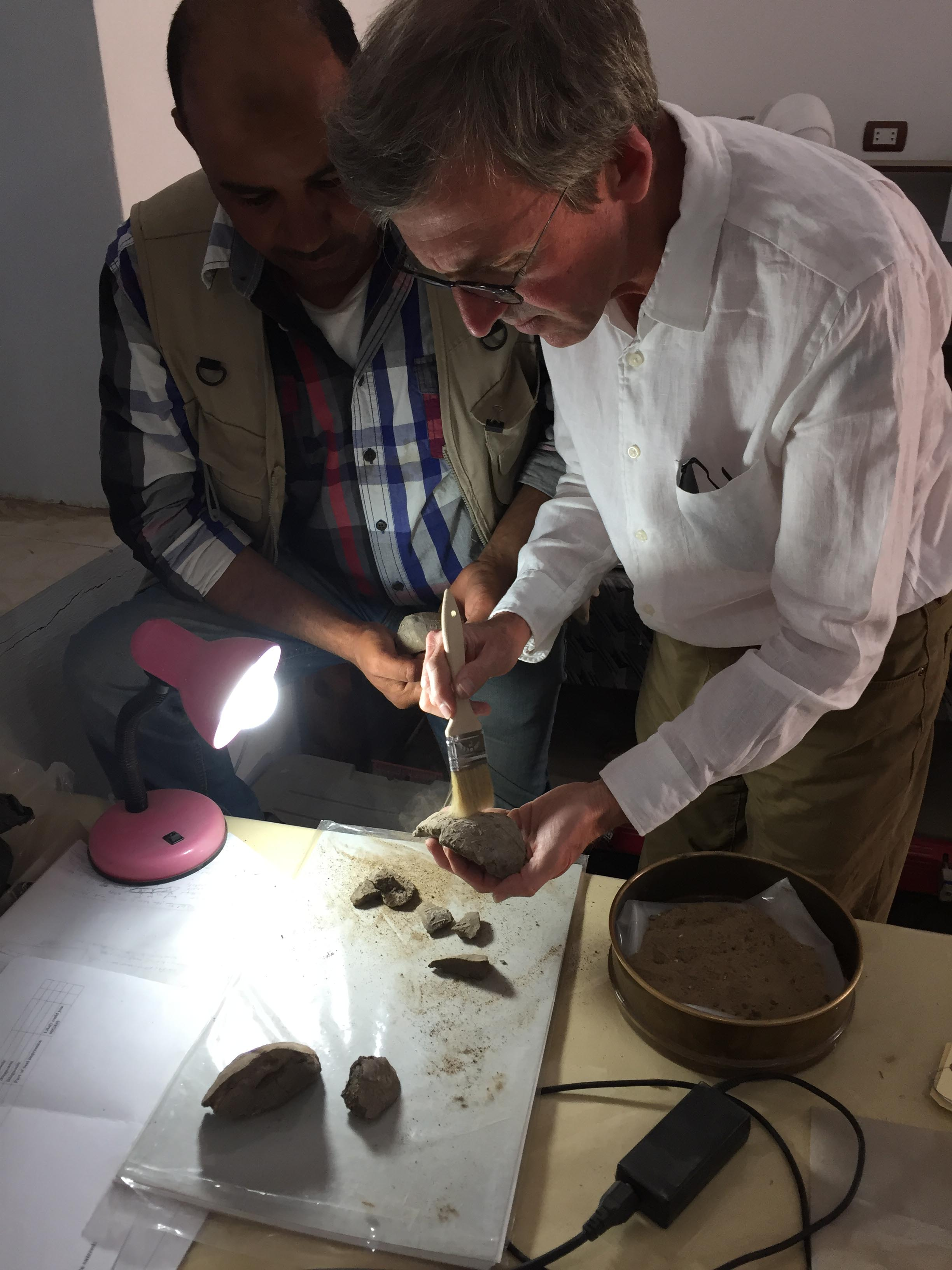 Fig. 11. Archaeologists Mohamed Abu el-Yazid and Matthew Adams examine seal impressions in the lab. Photo: Wendy Doyon © North Abydos Expedition 2019