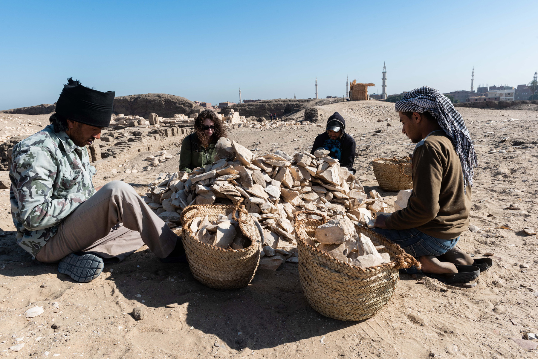Fig. 17. Sorting limestone fragments collected on the surface of the temple area. Photo: Ayman Damarany © North Abydos Expedition 2019