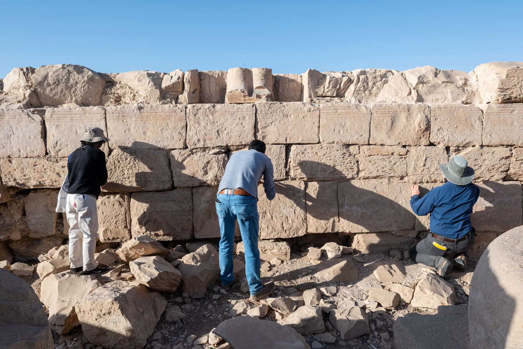 Fig. 14. Senior conservator Hiroko Kariya (left), archaeologist and photographer Ayman Damarany (center), and archaeologist Jo Young (right) setting the reference points for photo elevations along the inner, transverse columned hall of the temple. Photo: Logan Dean © North Abydos Expedition 2019
