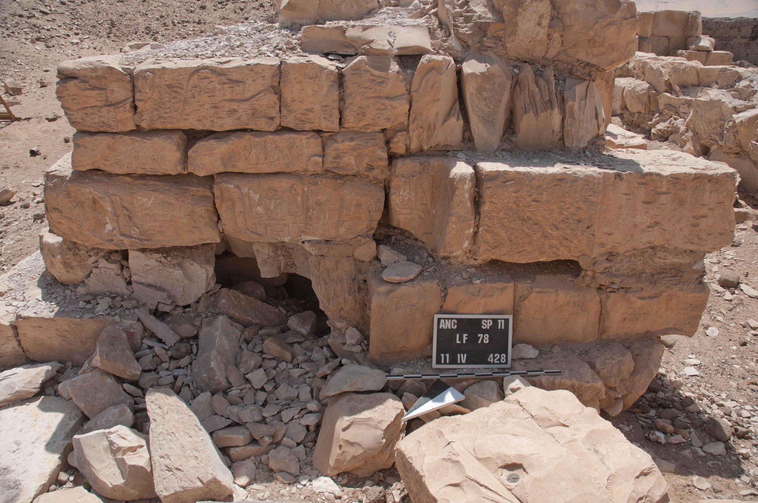 Fig. 13. Recent tunneling by vandals into the bottom corner of the southern wall of the temple passageway, opposite the wall pictured in Fig. 12. Photo: Greg Maka © North Abydos Expedition 2011