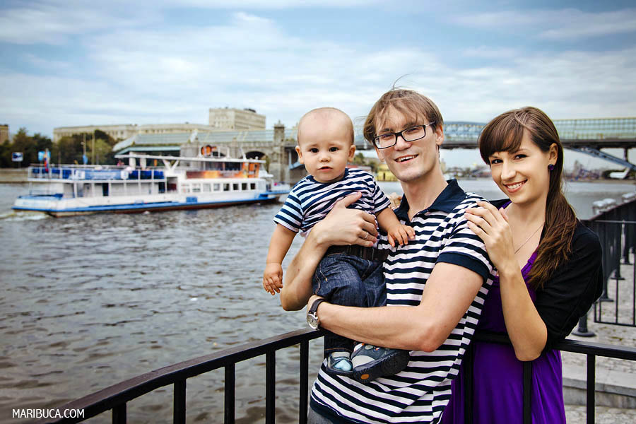 the ten-month-old son and dad wear marine-themed shirts such as dark blue and white stripes, and my mother wears a purple dress. They stand against the background of the river and the ship sails behind them.