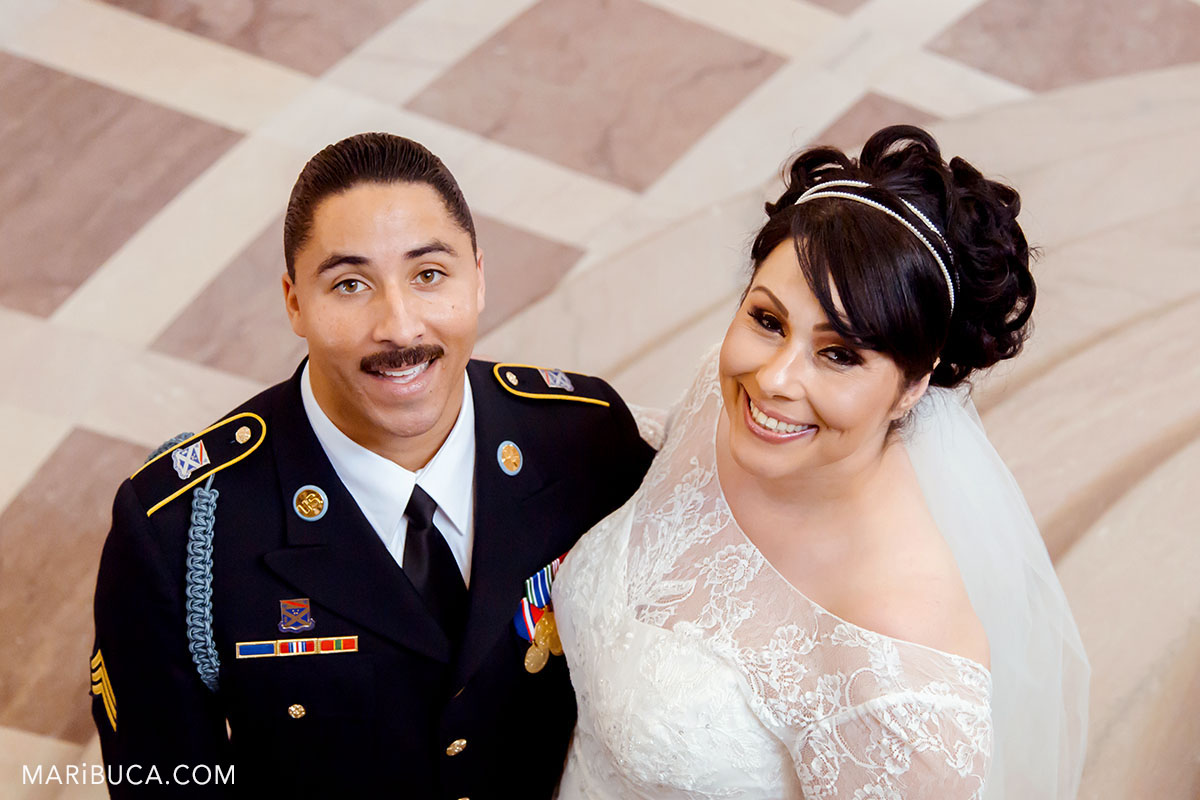The bride and groom smile and look up in the sf city hall california