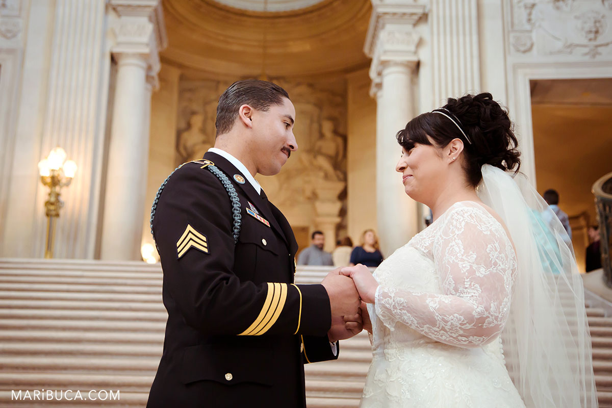 Bride and groom are holding hands and looks each other in the stairs and white architecture background of San Francisco City Hall