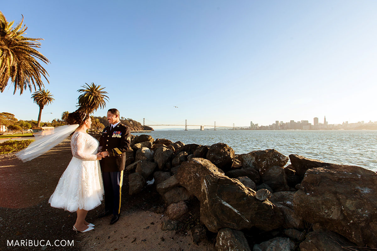 Newlyweds hubby and wifey look each other during the orange sunset in the treasure island, san francisco wedding