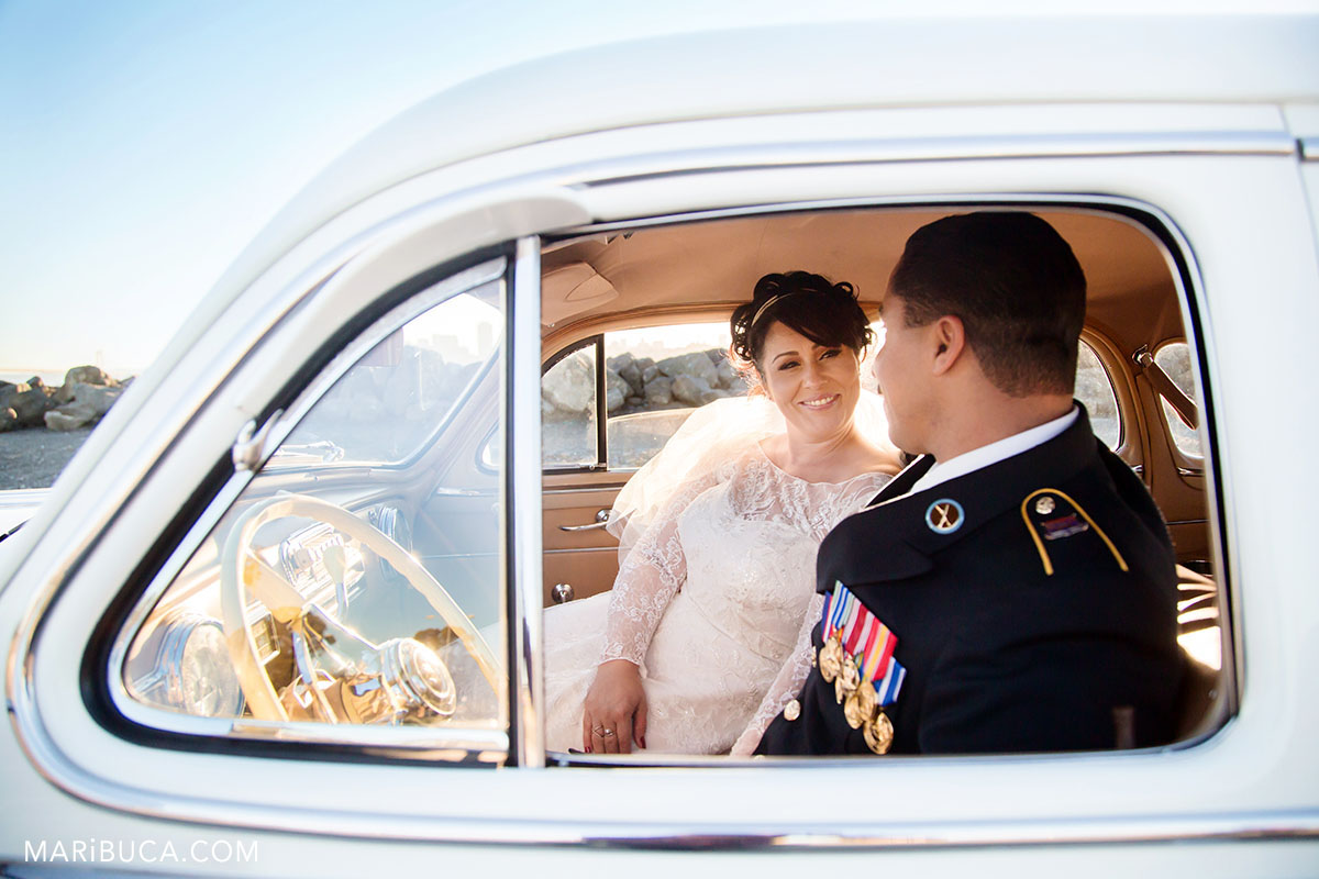 bride looking at the groom and they both are sitting in the pontiac in the Treasure Island, California