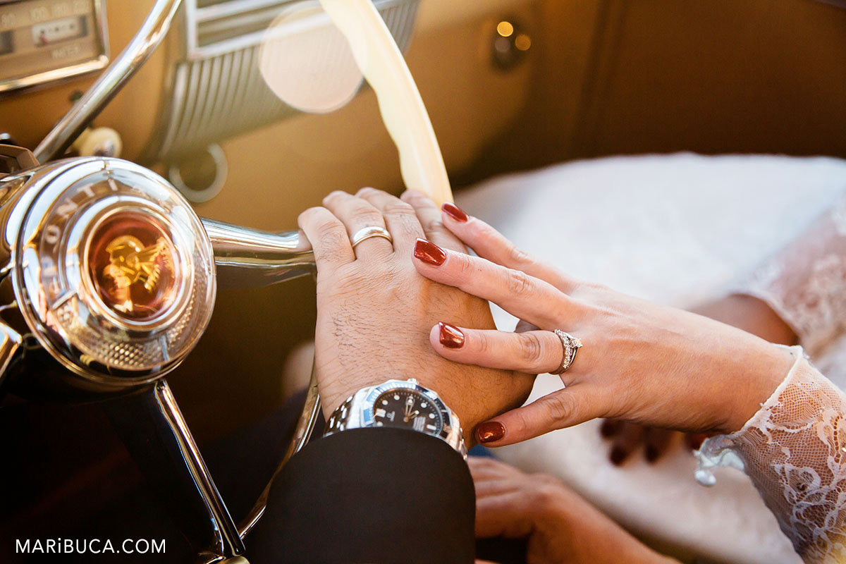 wedding detail inside the pontiac car: newlyweds hands with wedding rings, watch and wheel with sign Pontiac.