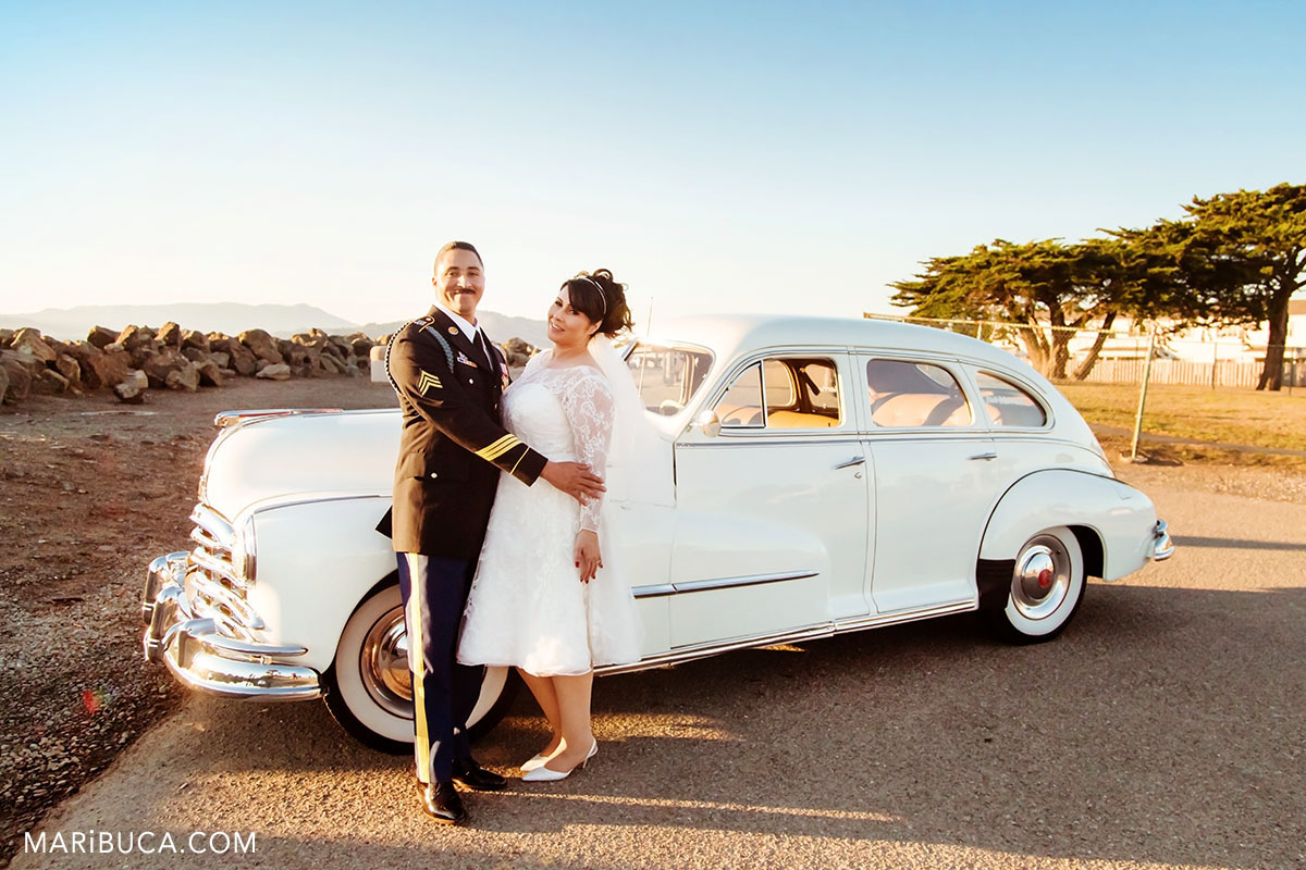 Beautiful sunset and just married couple and behind stays white Pontiac car in the Treasure island